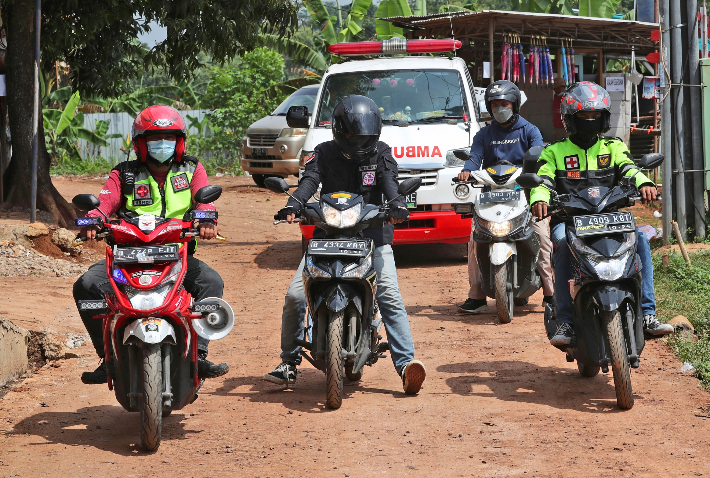 Four people on motorbikes are shown wearing helmets with an ambulance driving behind them.