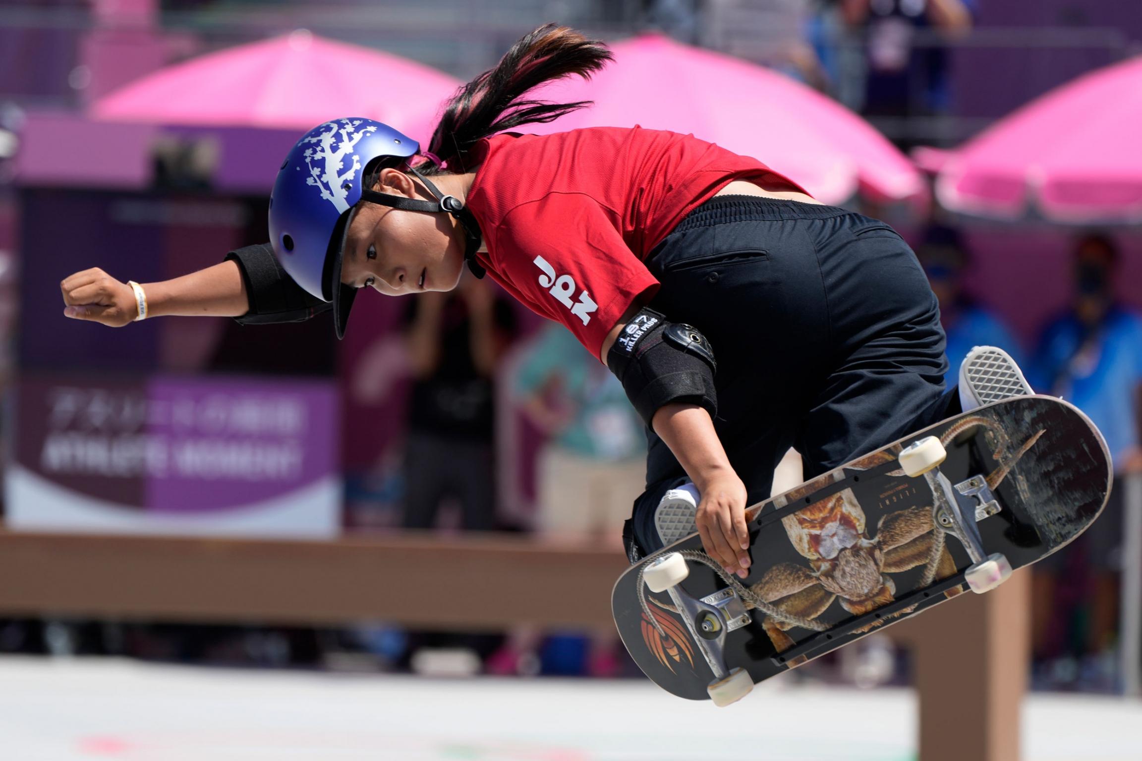 Sakura Yosozumi is shown in mid-air holding her skateboard to her feet.