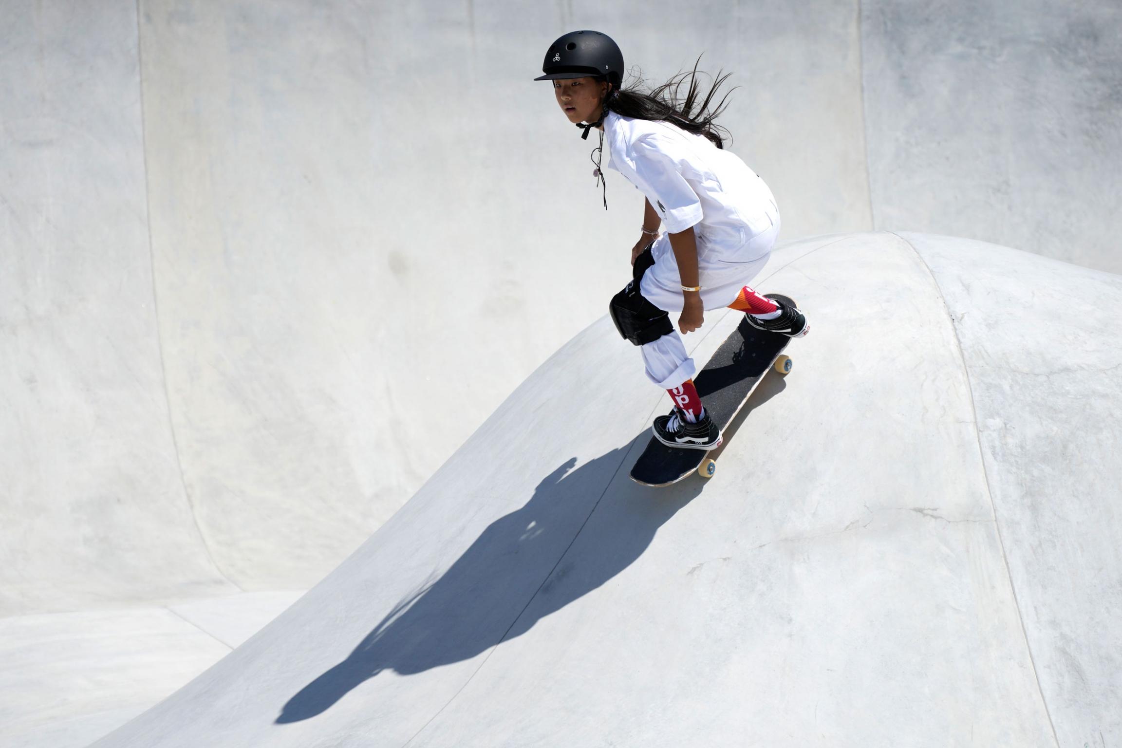 Kokona Hiraki is shown wearing all white and black knee pads while riding a skateboard.