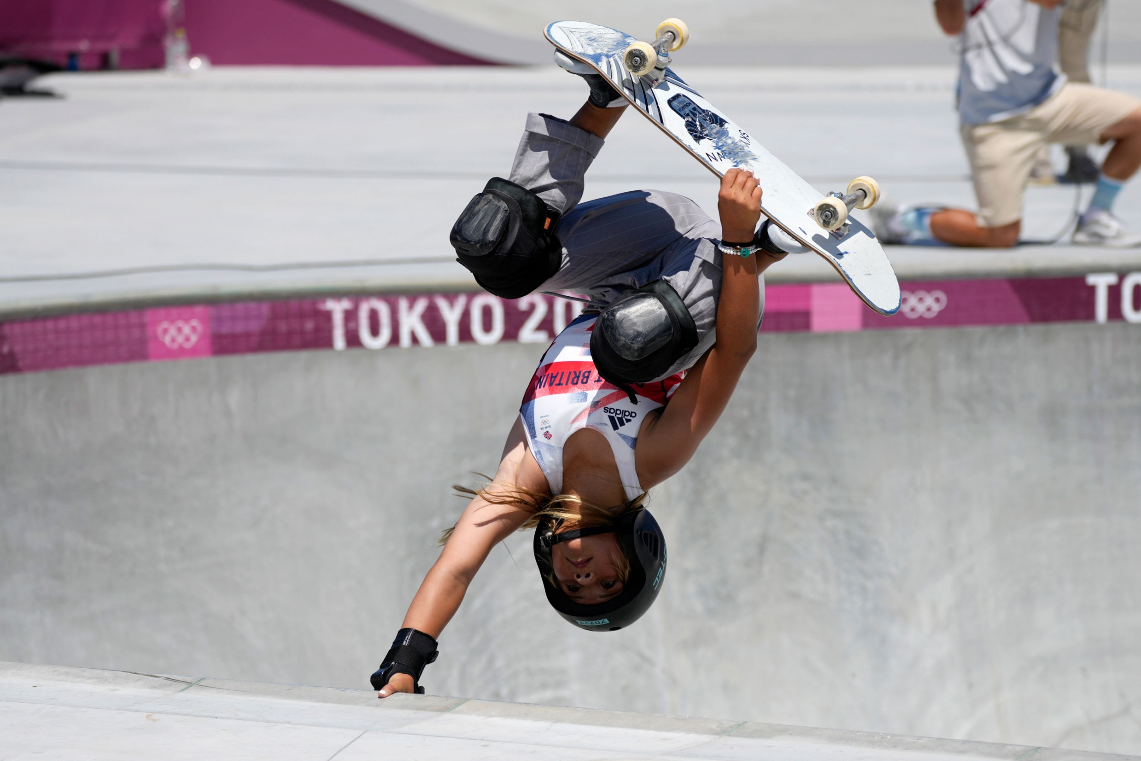Sky Brown of Britain is shown upside down with her skateboard held against her feet and her right arm holding on to the edge of the park bowl.