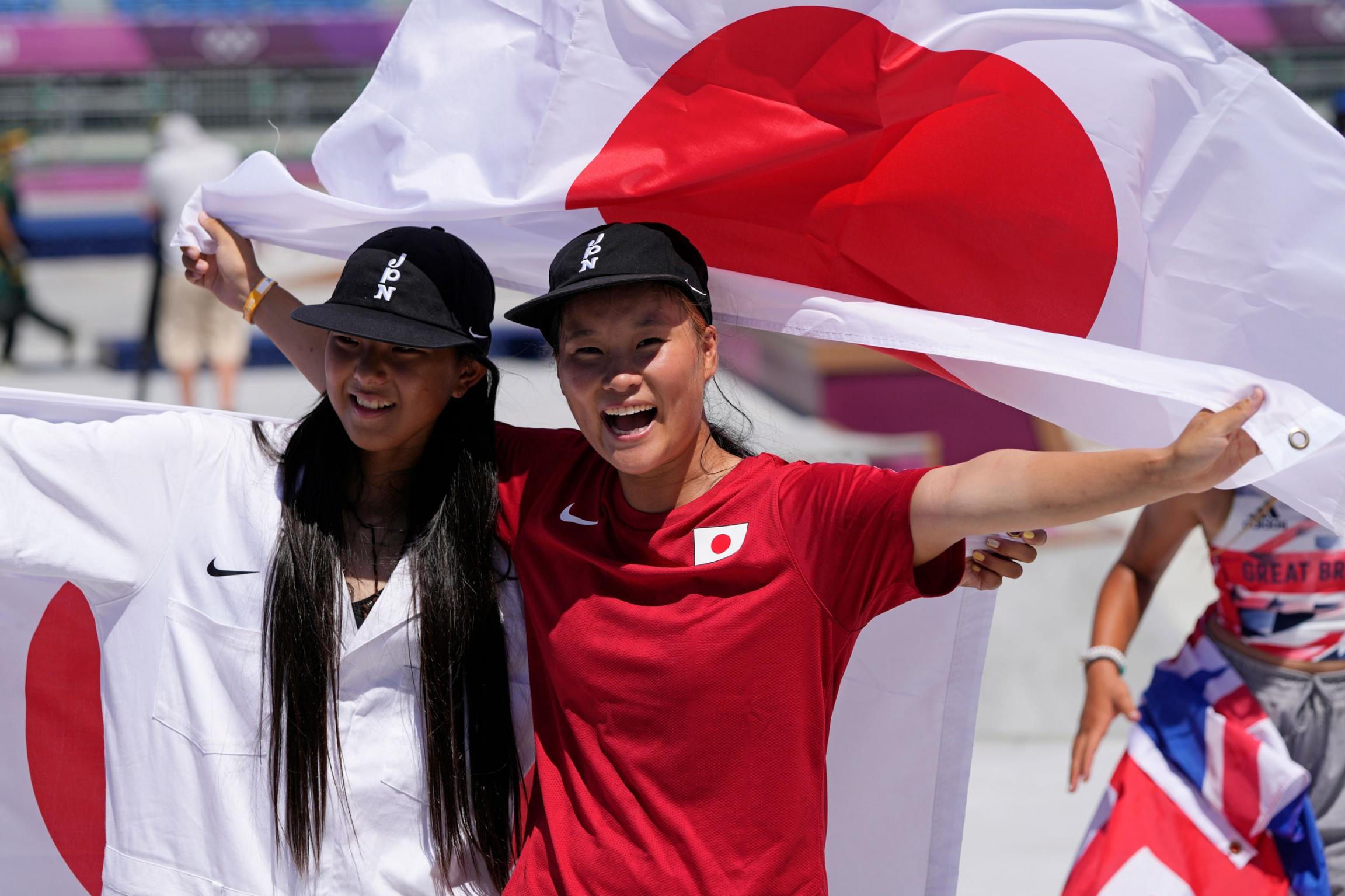 Sakura Yosozumi and Kokona Hiraki are show side-by-side with a Japanese flag held up behind them.