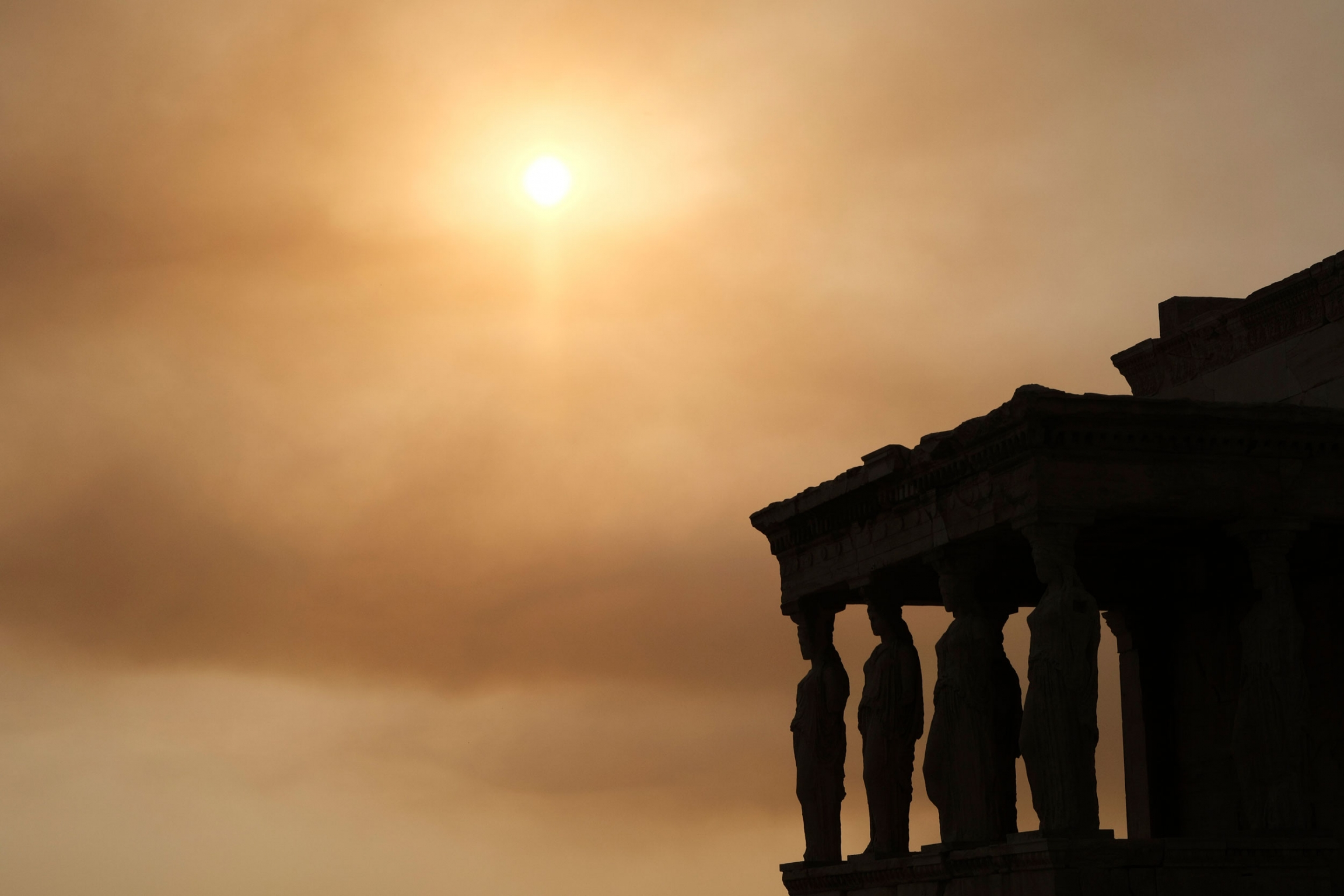 The columns of the Acropolis are shown in shadown with the sun in the distance blocked by smoke clouds.