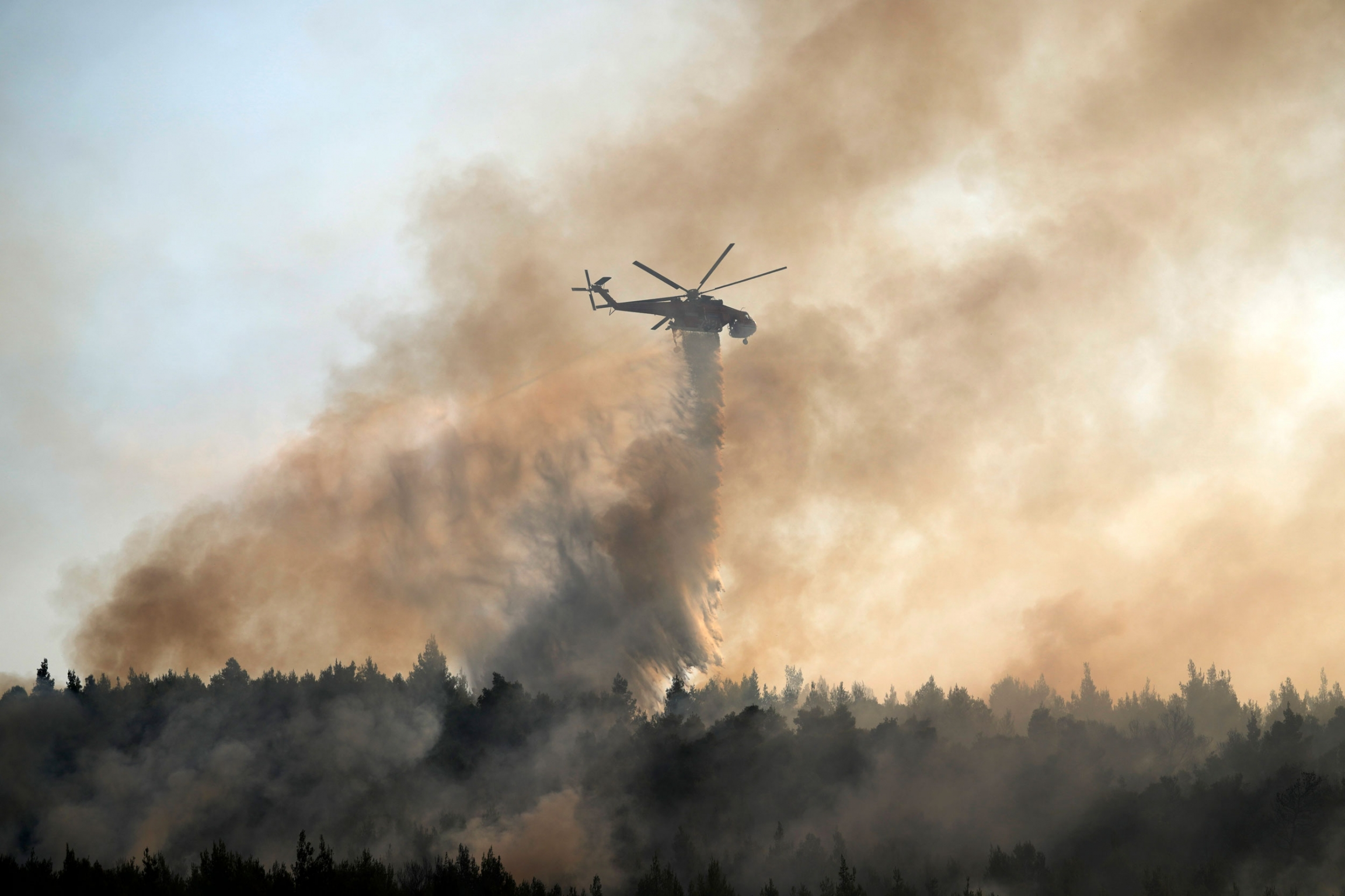 A helicopter is shown in the distance amid smoke rising up from the forest below.
