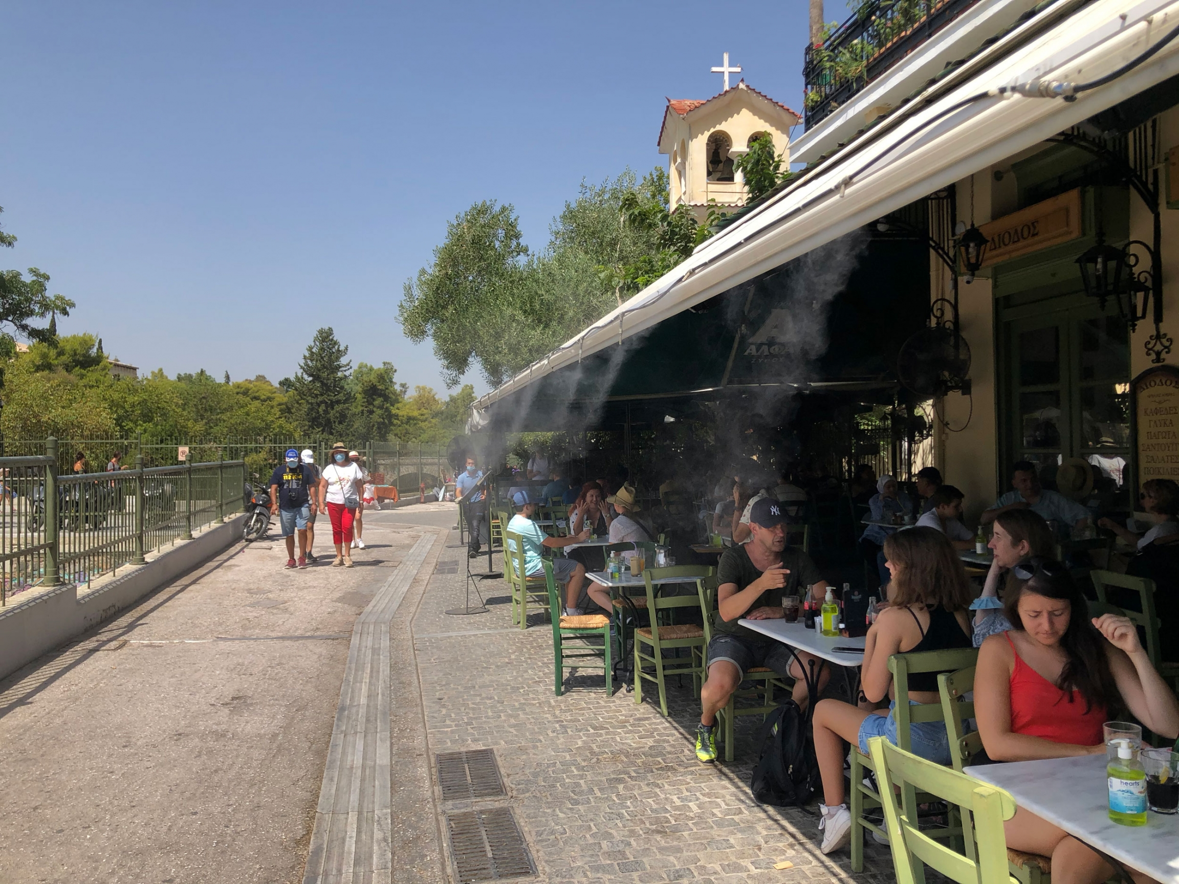 Patrons of a open-air restaurant are shown with several spigots at the roof line spraying mist.