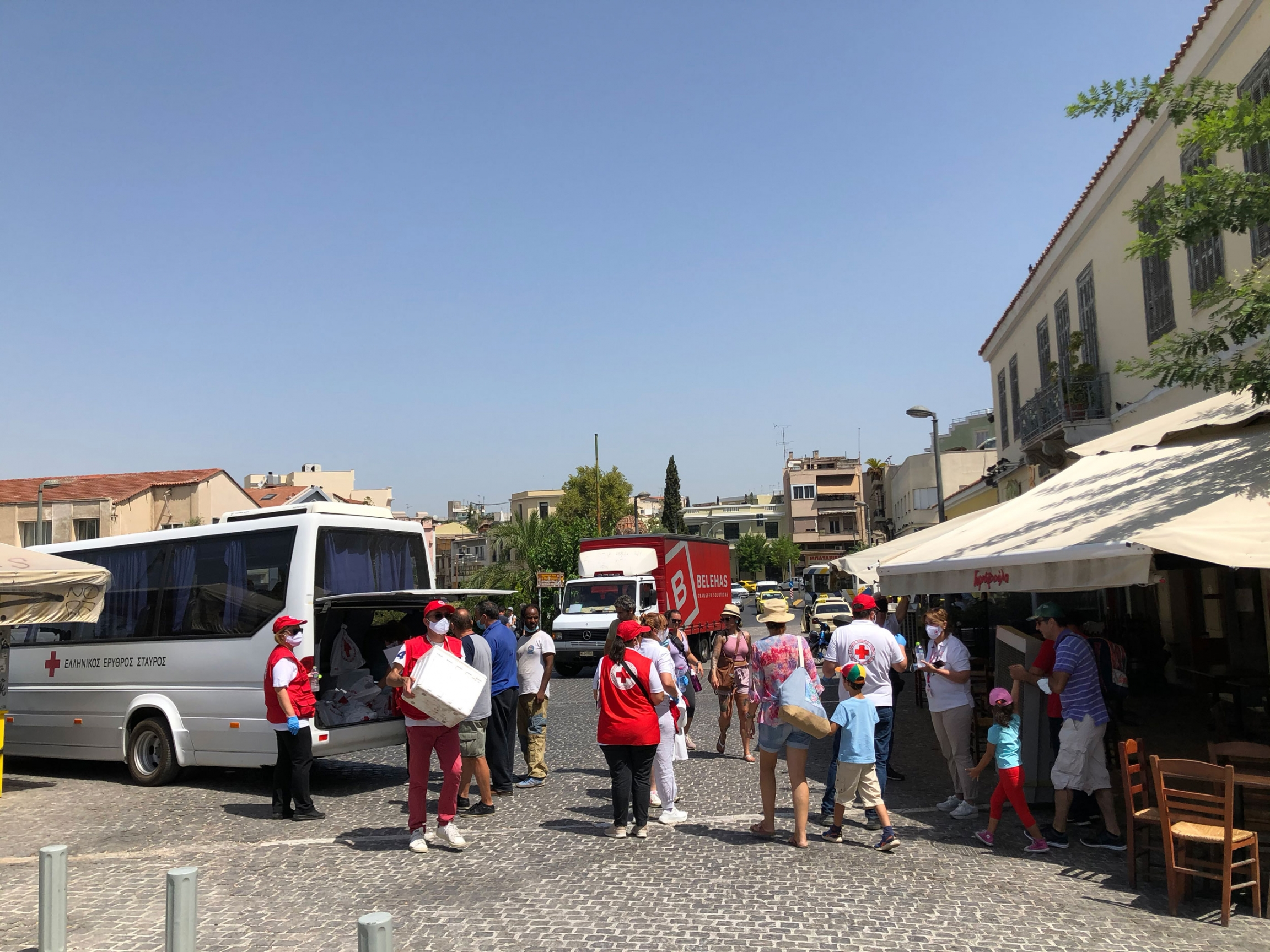 A white van with a red cross on it is shown with the back doors open and several people outside handing out water.