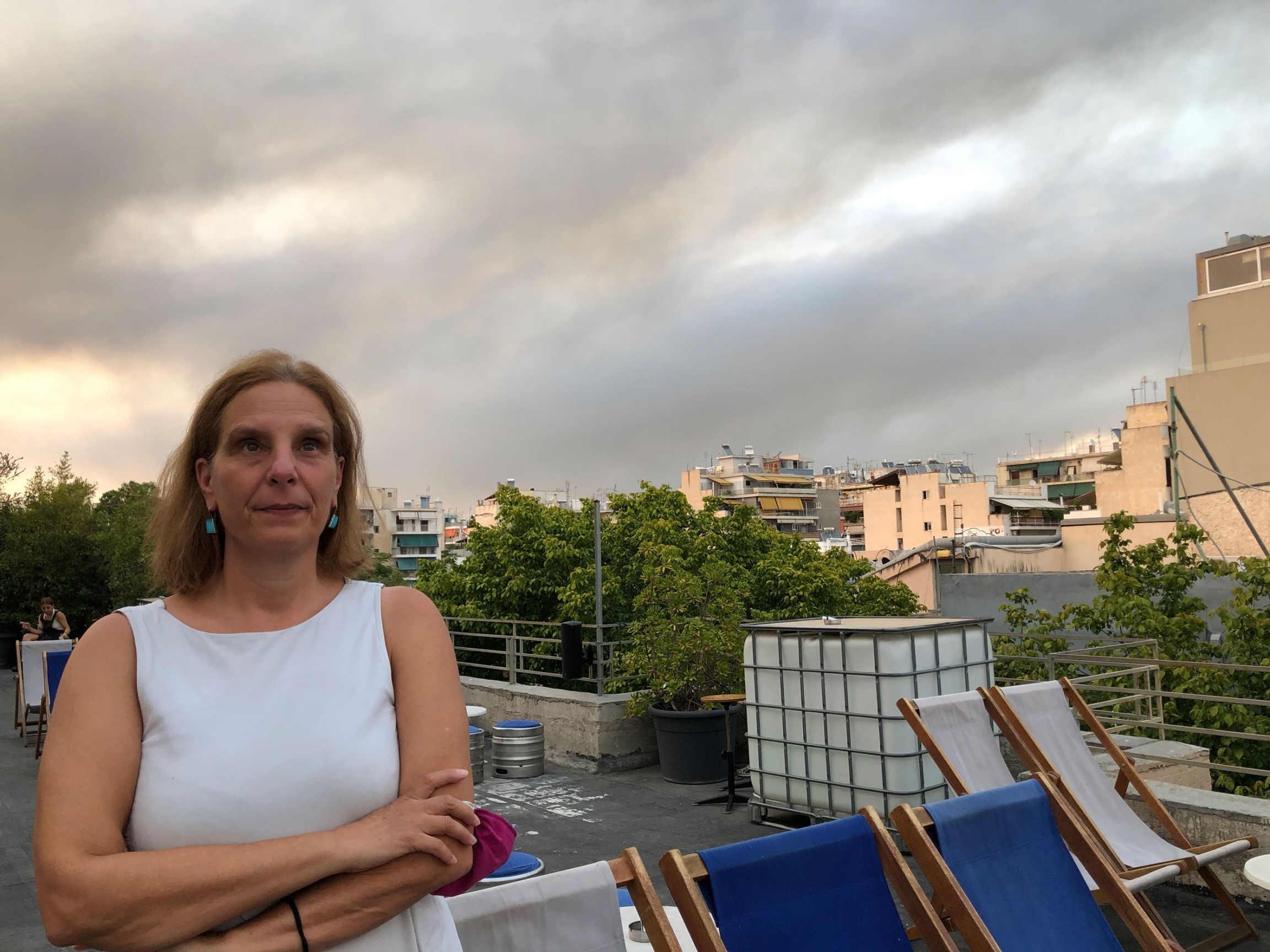 Eleni Myrivili is shown wearing a white sleeveless shirt while standing on a rooftop with the sky behind her filled with smoke clouds.