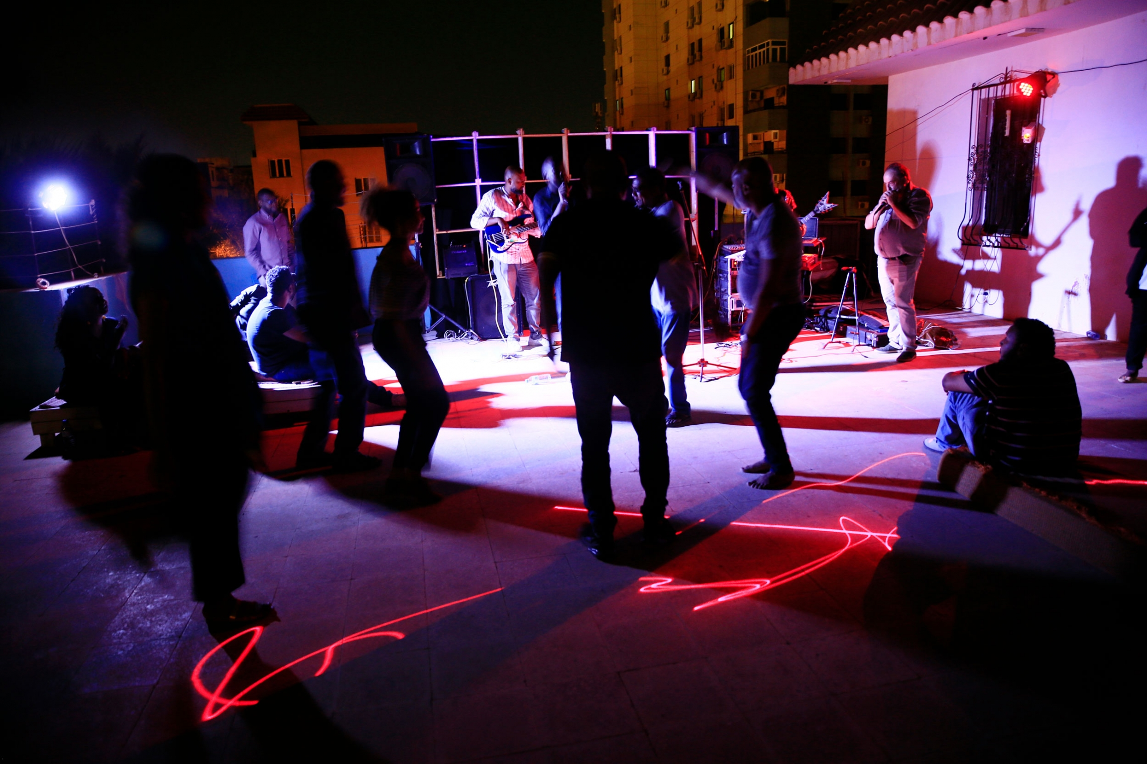 A crowd of people are shown in purple and red lighting, dancing with a band playing in the distance.