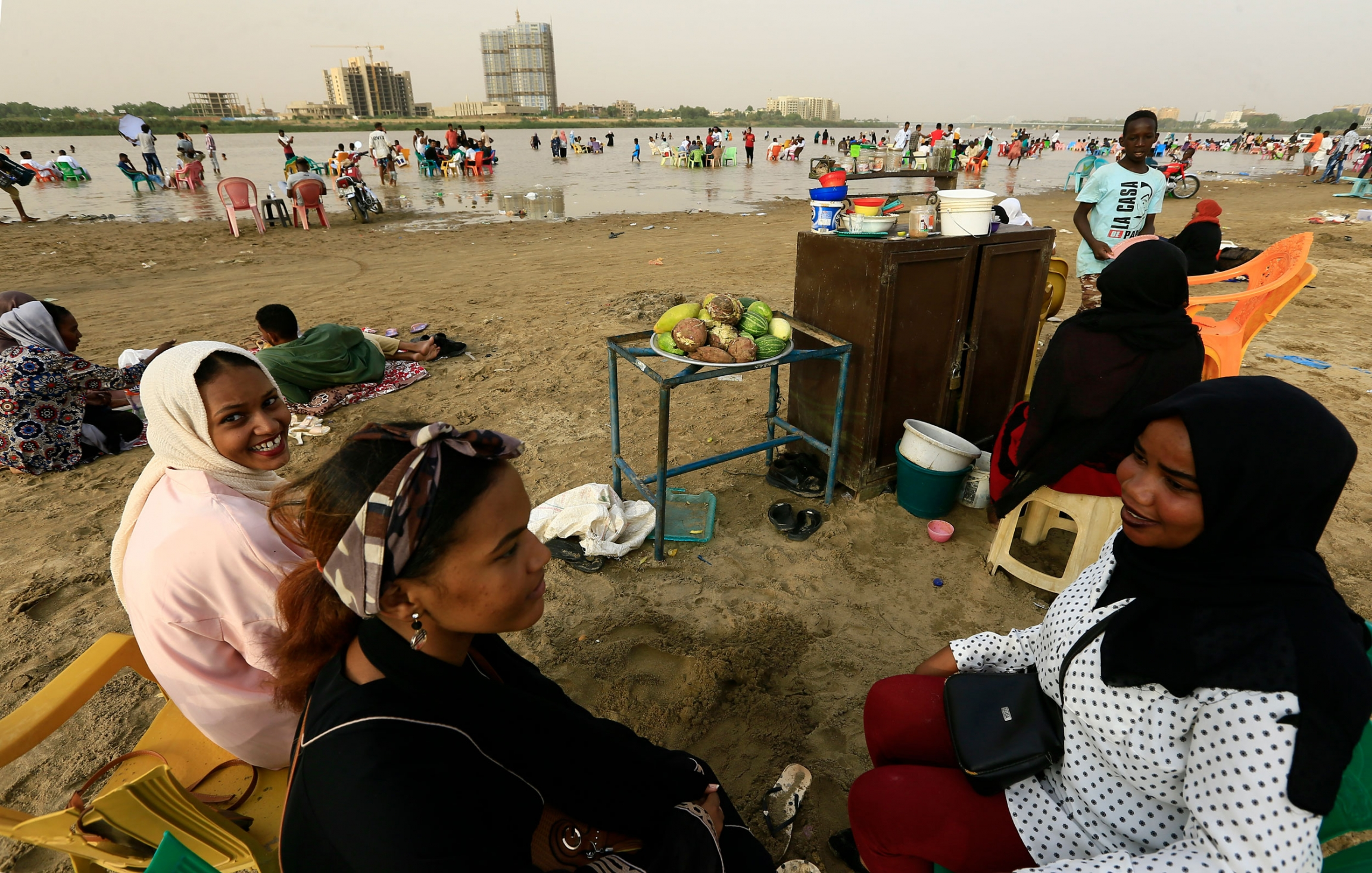 A group of three women are shown sitting with food nearby and the Nile River in the distance.