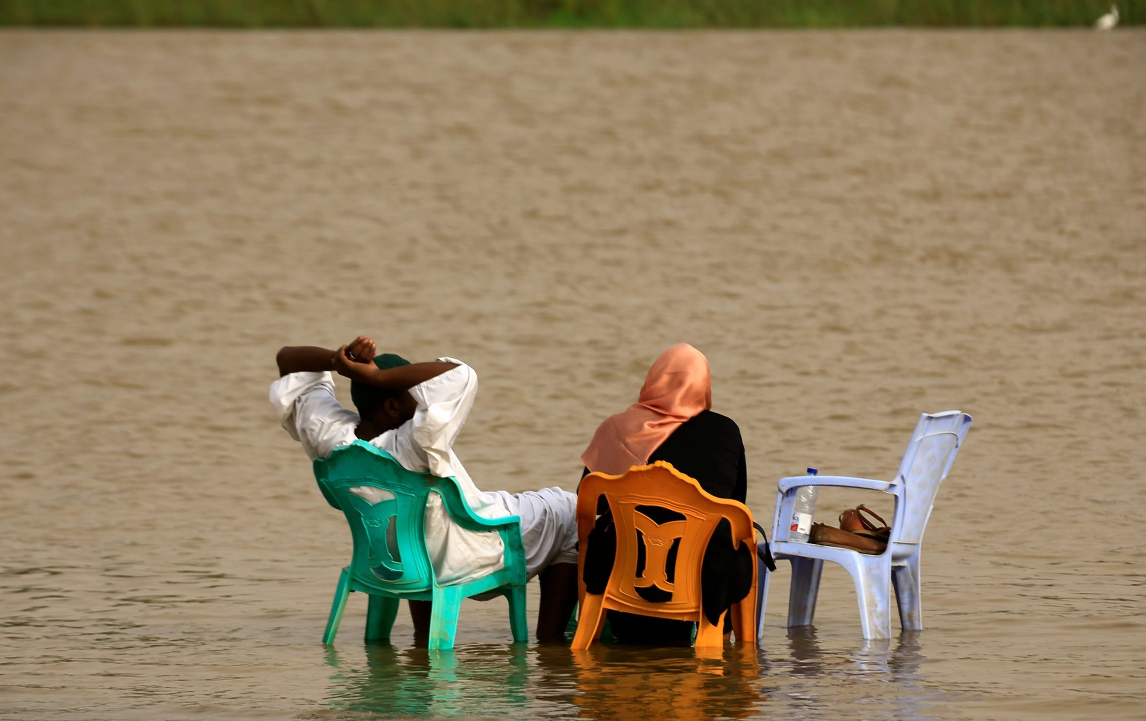 A man and woman are shown from behind both sitting in plastic chairs submerged in the water to their ankles.