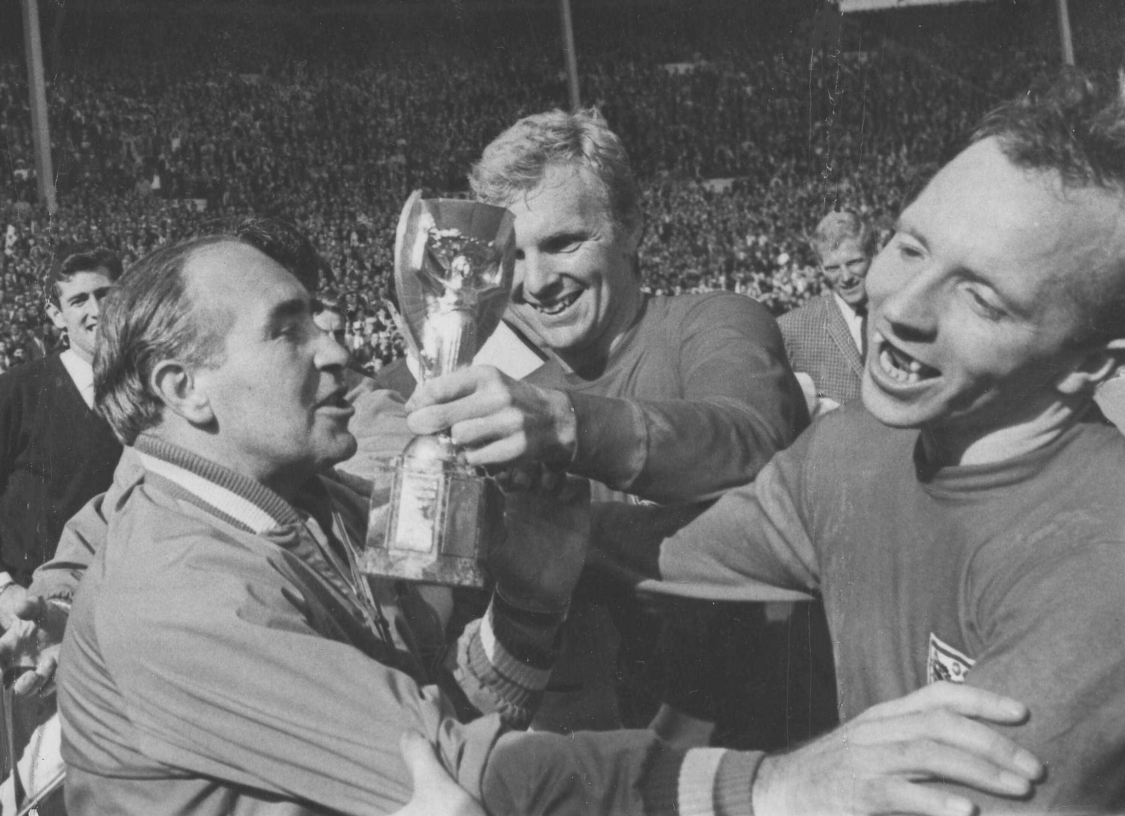 In this July 30, 1966 file photo, England midfield player Nobby Stiles, right, looks at the Jules Rimet Cup, held by England captain Bobby Moore after they had won the World Cup Final at Wembley, London.