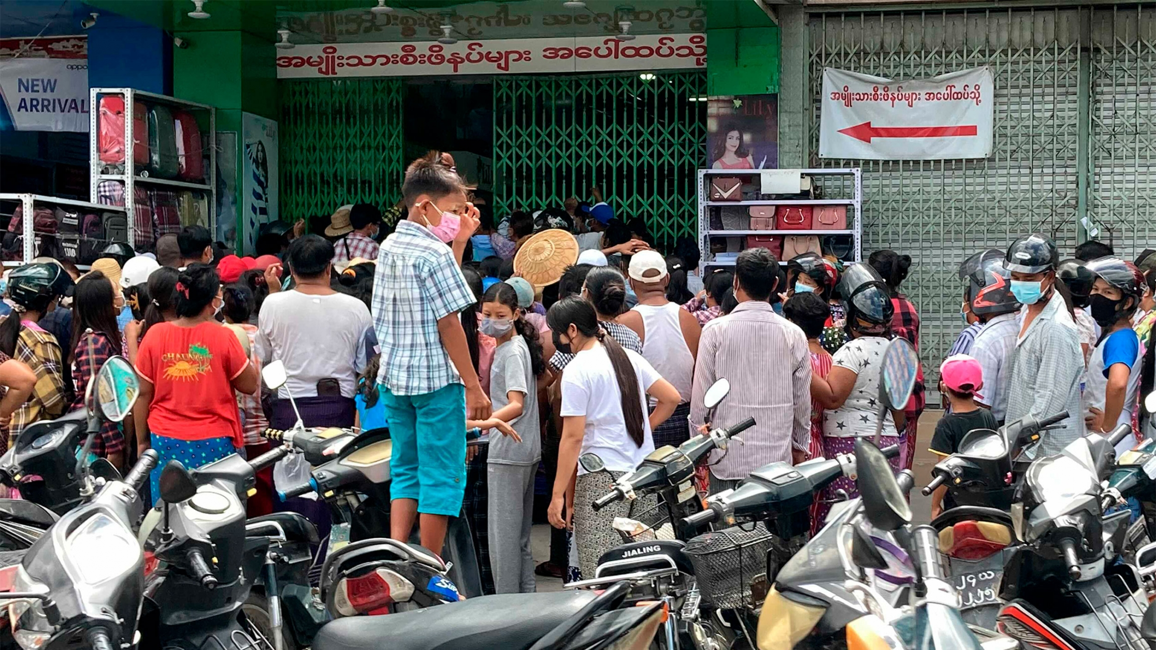People wait outside a shop where face masks and vitamins are being given away in Mandalay, Myanmar