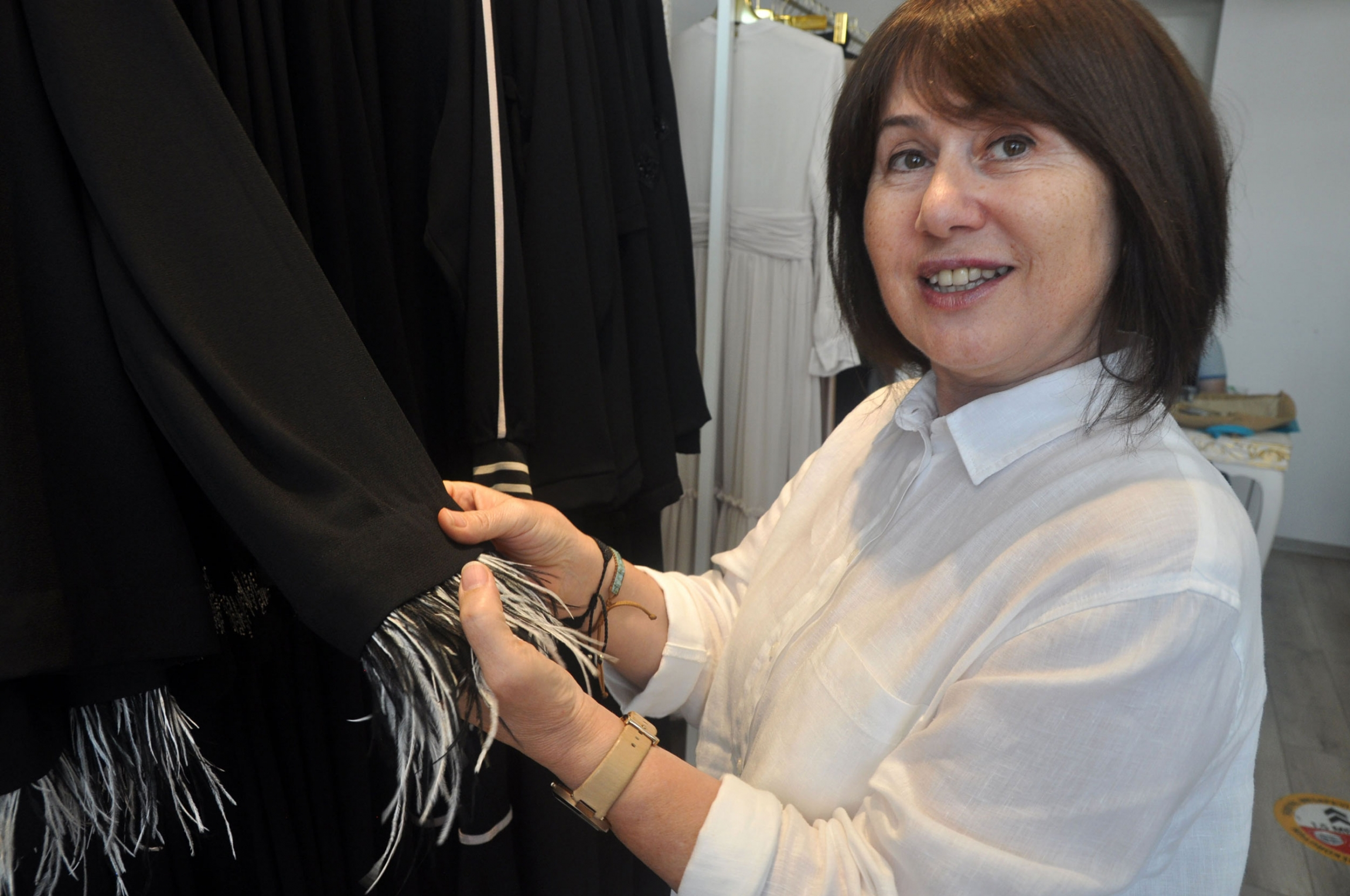 Ayşe Yıldırım explains a detail on one of her designs: a feathered, removable cuff.