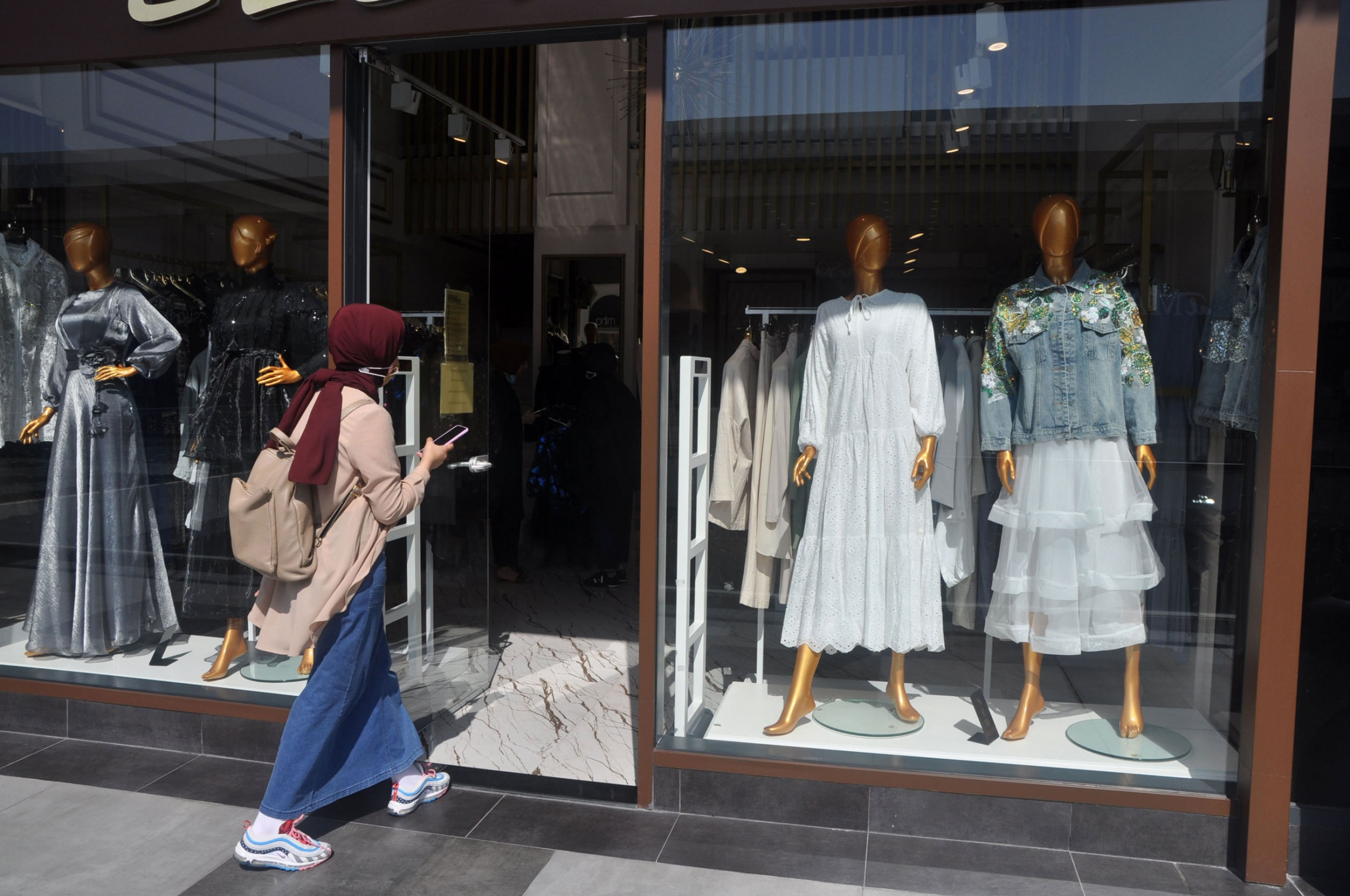 A woman enters a modest fashion clothing store in Istanbul.