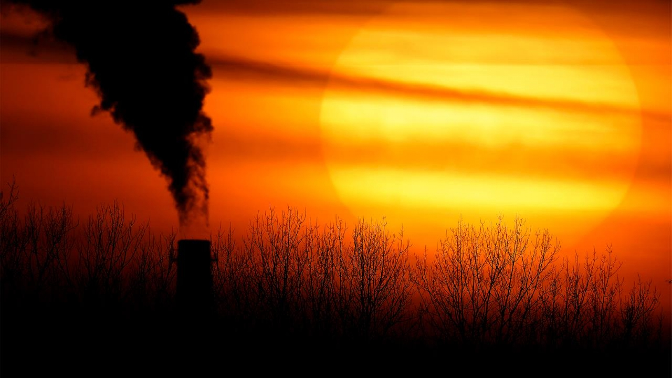 Emissions from a coal-fired power plant are silhouetted against the setting sun in Independence, Mo.