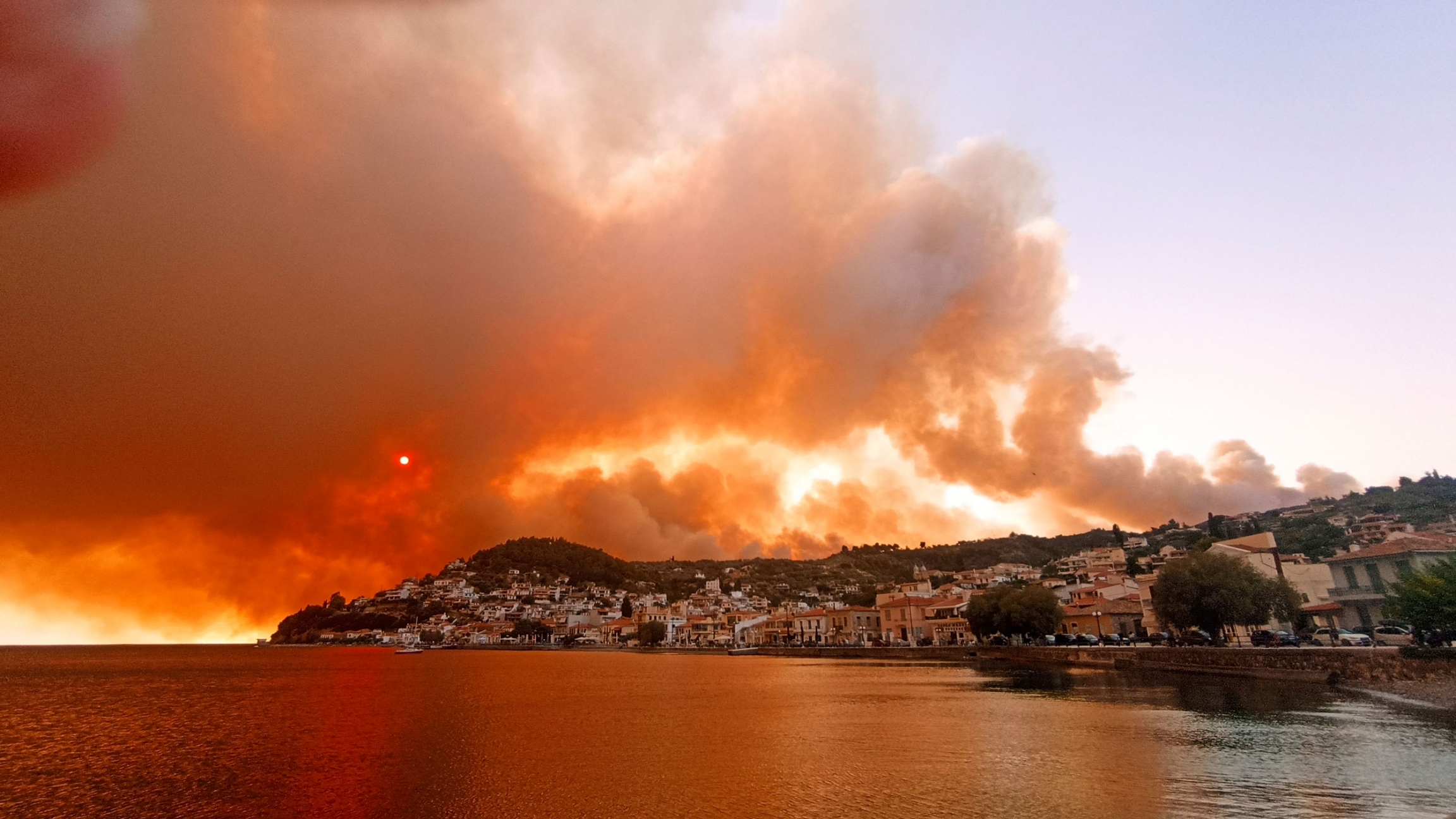 The shoreline of a village on the Greek island of Evia is shown with massive plumes of dark smoke rising in the distance.