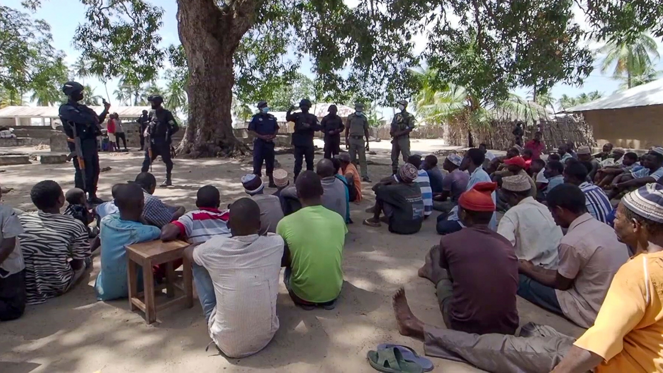 In this image made from video, Rwandan and Mozambican police speak to returnees in Palma, Cabo Delgado province, Mozambique