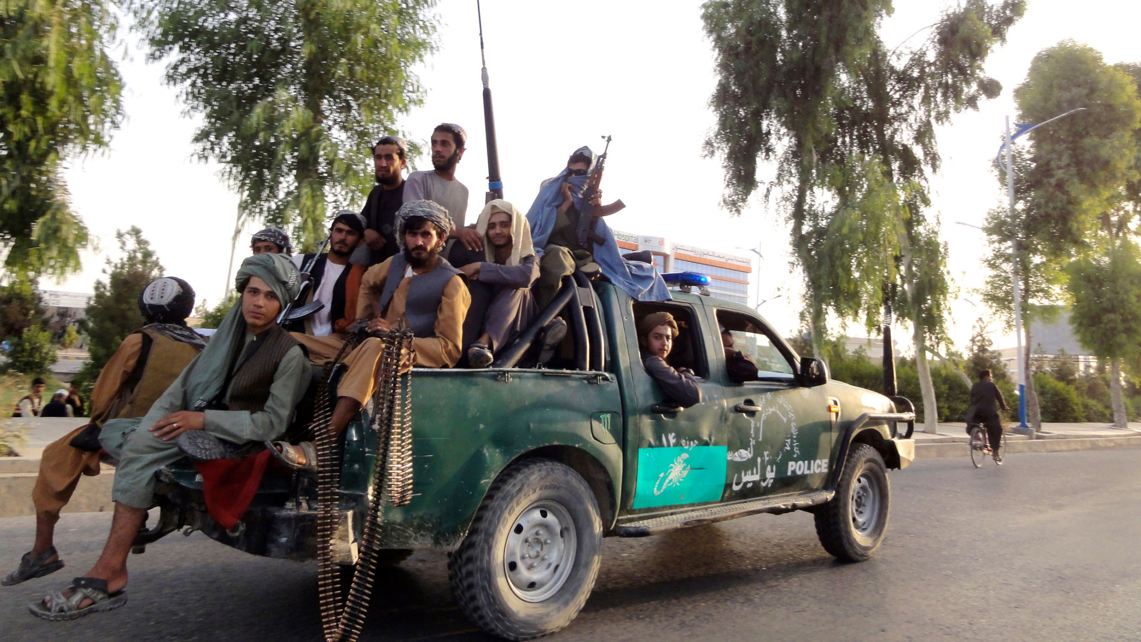 Several Taliban fighters are shown sitting in the back of a pickup truck, several holding weapons.
