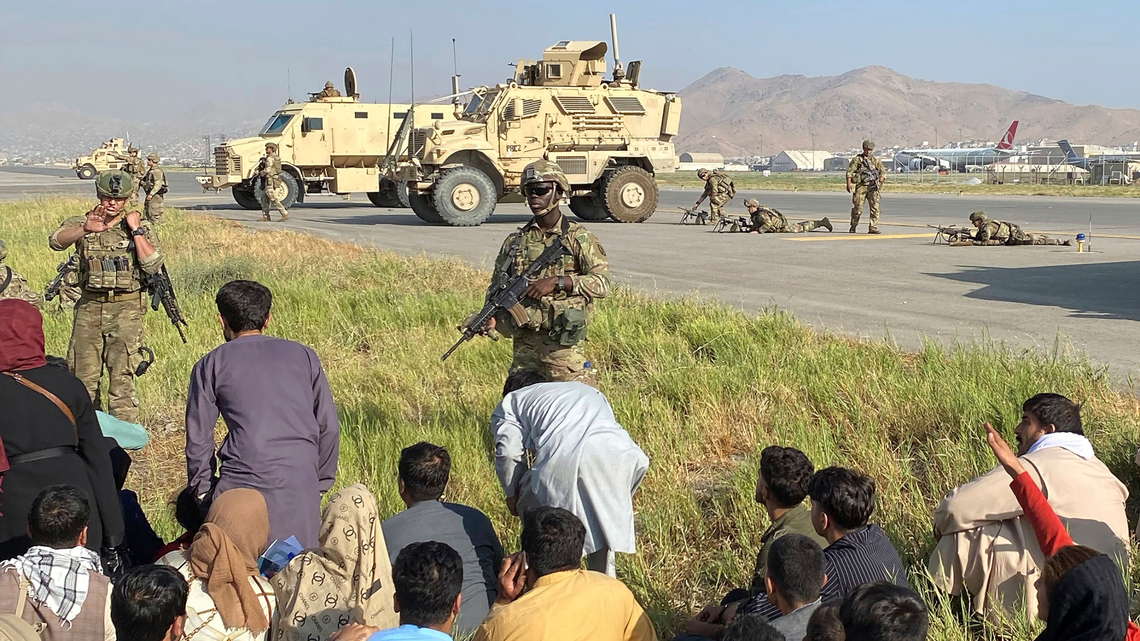Several US military personnel are show standing guard next to the runways of the Kabul airport with two large military vehicles in the distance.