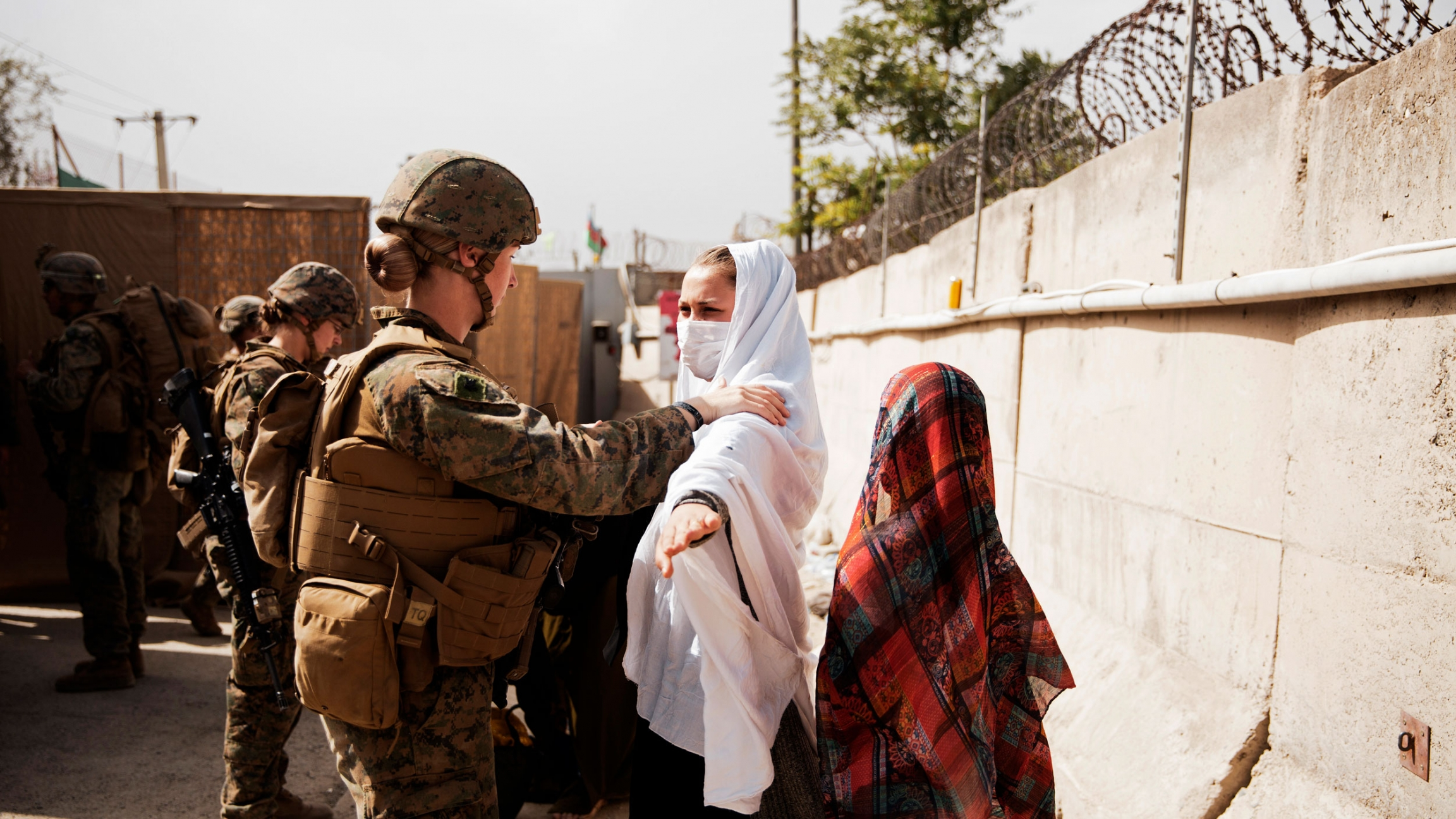 In this photo provided by the US Marine Corps, two civilians during processing through an Evacuee Control Checkpoint during an evacuation at Hamid Karzai International Airport, in Kabul, Afghanistan, Wednesday, Aug. 18, 2021.