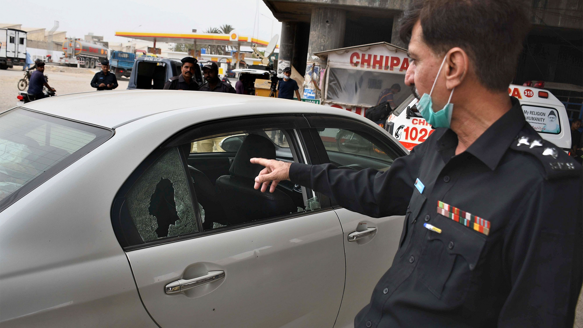 A police officer examines a damaged car at the site of a firing incident, in Karachi, Pakistan