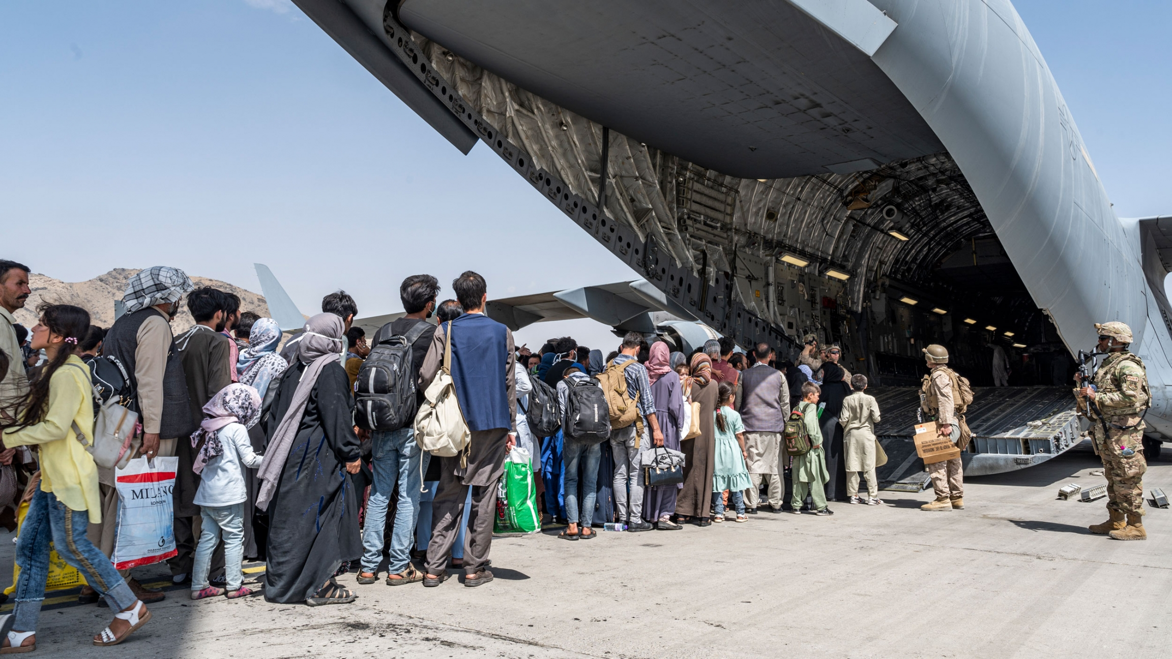 In this Aug. 21, 2021, image provided by the U.S. Air Force, US Airmen and U.S. Marines guide evacuees aboard a U.S. Air Force C-17 Globemaster III in support of the Afghanistan evacuation at Hamid Karzai International Airport in Kabul, Afghanistan.