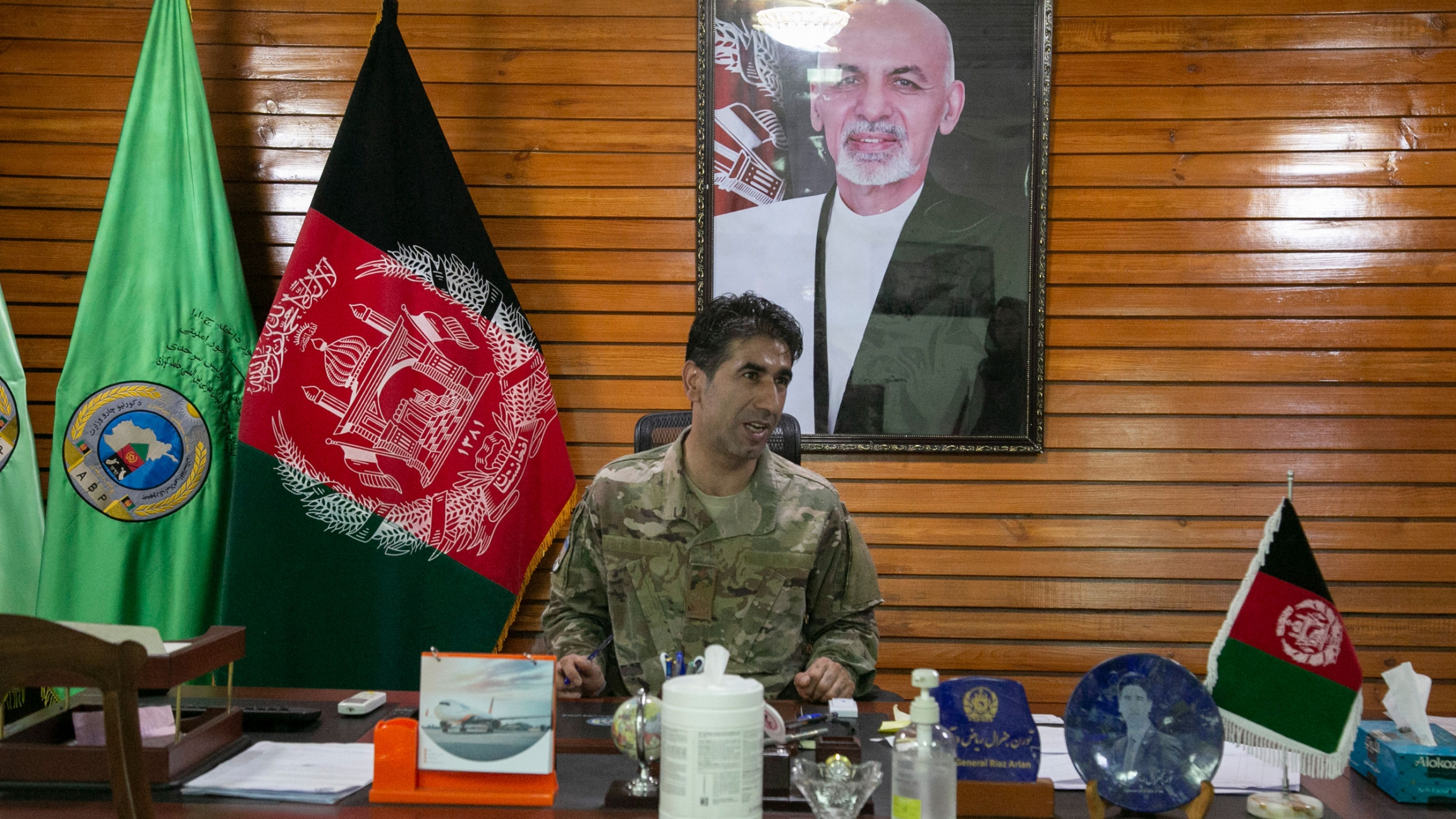 Maj. Gen. Mohammad Reyaz Arian is shown sitting at a large wooden desk and wearing military fatigues with the Afghanistan flag and a portrait photo of former President Ashraf Ghani on the wall.