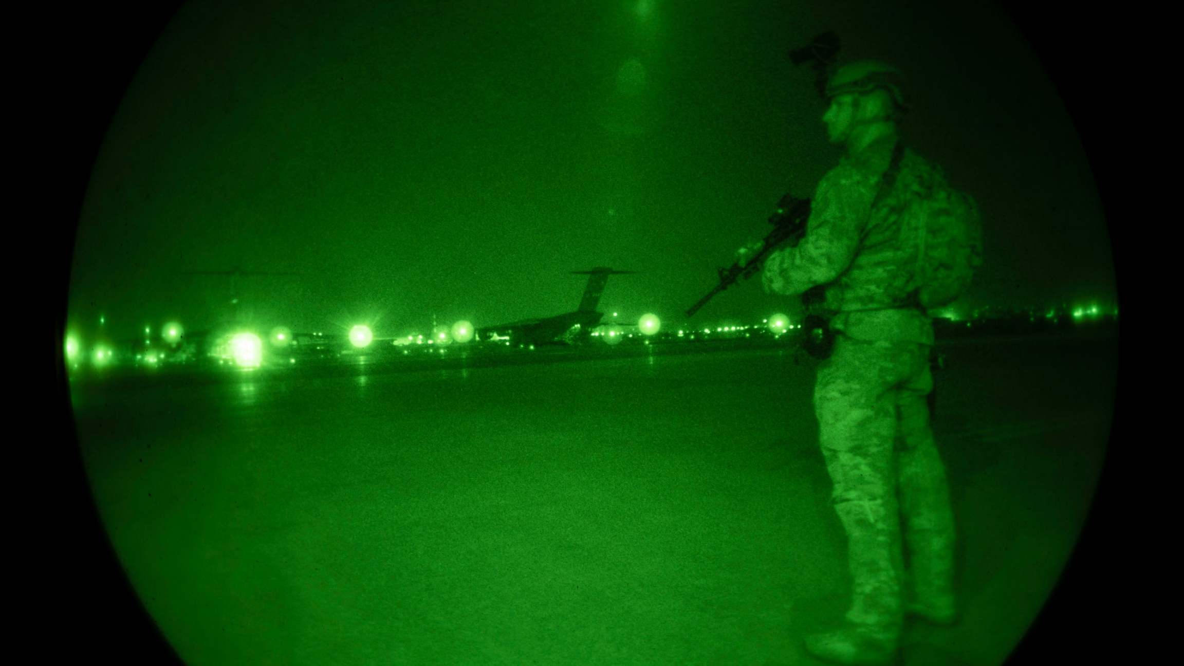 In this Aug. 22, 2021, image provided by the US Air Force and made through a night vision scope, a USAir Force security forces raven, assigned to the 816th Expeditionary Airlift Squadron, maintains a cordon around a US Air Force C-17 Globemaster III in s