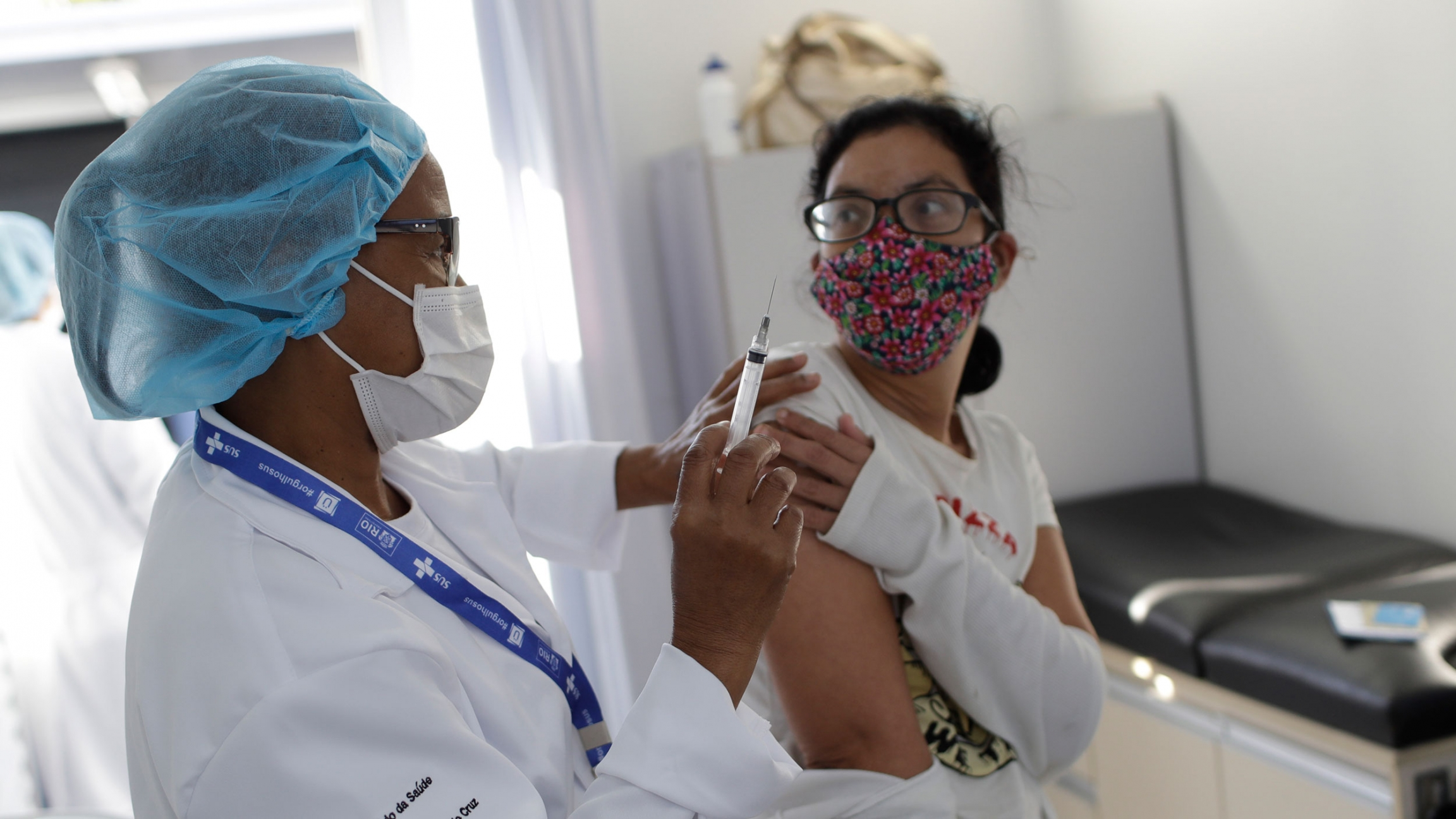 A resident gets a dose of the AstraZeneca vaccine on the first day of a three-day COVID-19 vaccination campaign for people over age 35 in the Complexo da Maré favela of Rio de Janeiro, Brazil, Brazil, Thursday, July 29, 2021.