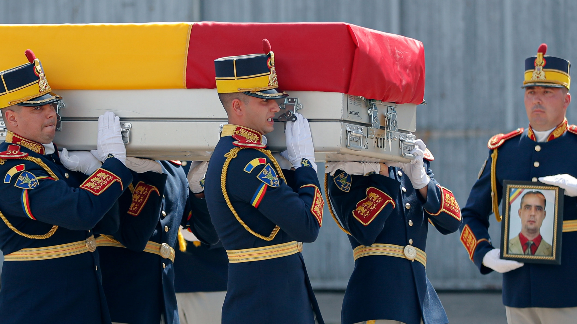 Honor guard soldiers carry the coffin of Vasile Raduna, seen in the photo on the right, during the ceremony for the repatriation his and of Corp. Ciprian-Stefan Polschi's body from Afghanistan, in Bucharest, Romania, Tuesday, Sept. 10, 2019.