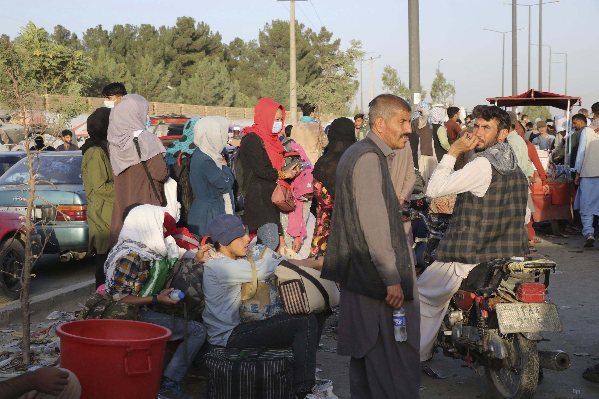 Hundreds of people gather near an evacuation control checkpoint during ongoing evacuations at Hamid Karzai International Airport, in Kabul.