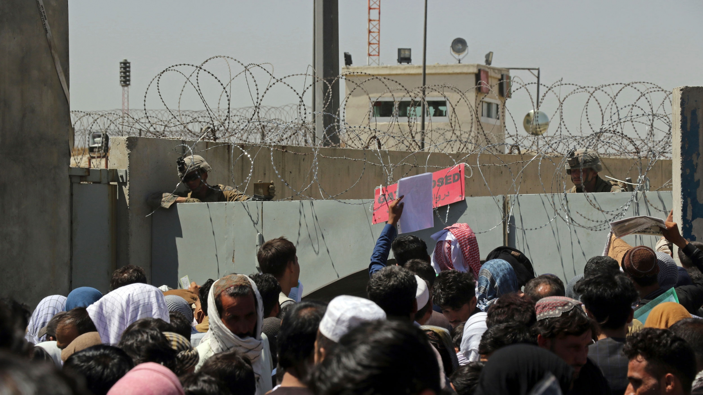 A larger crowd of people are shown crammed up against large cement barriers with barbed-wire on top.