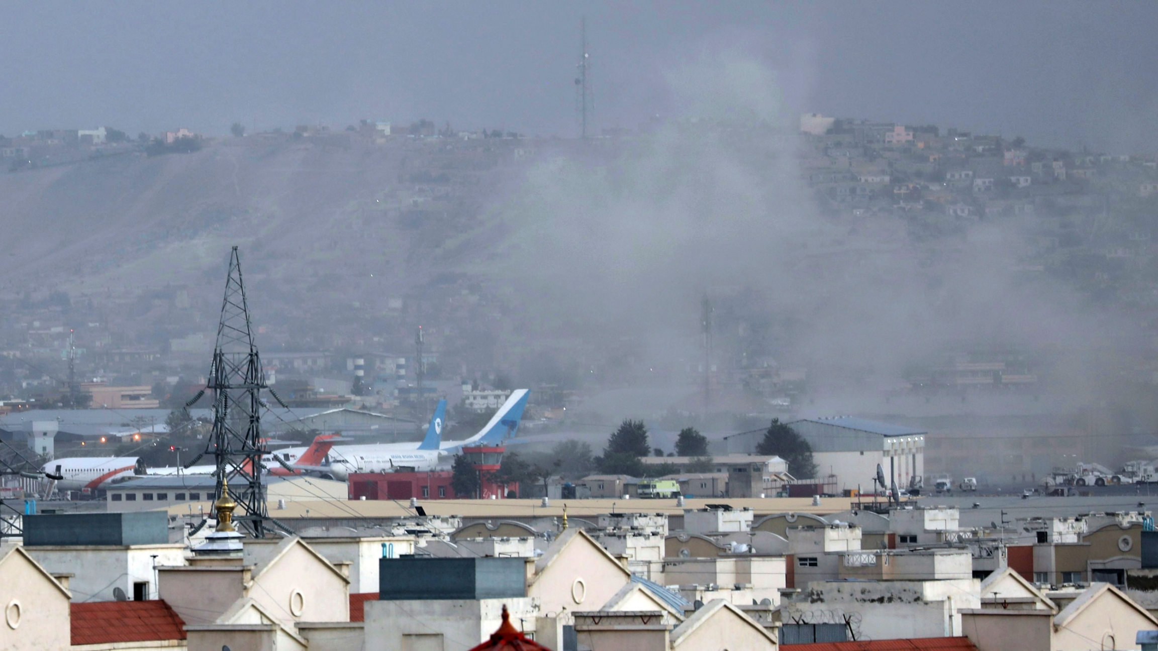 A wide-framed photograph is shown of Kabul with the airport in the distance and smoke rising.