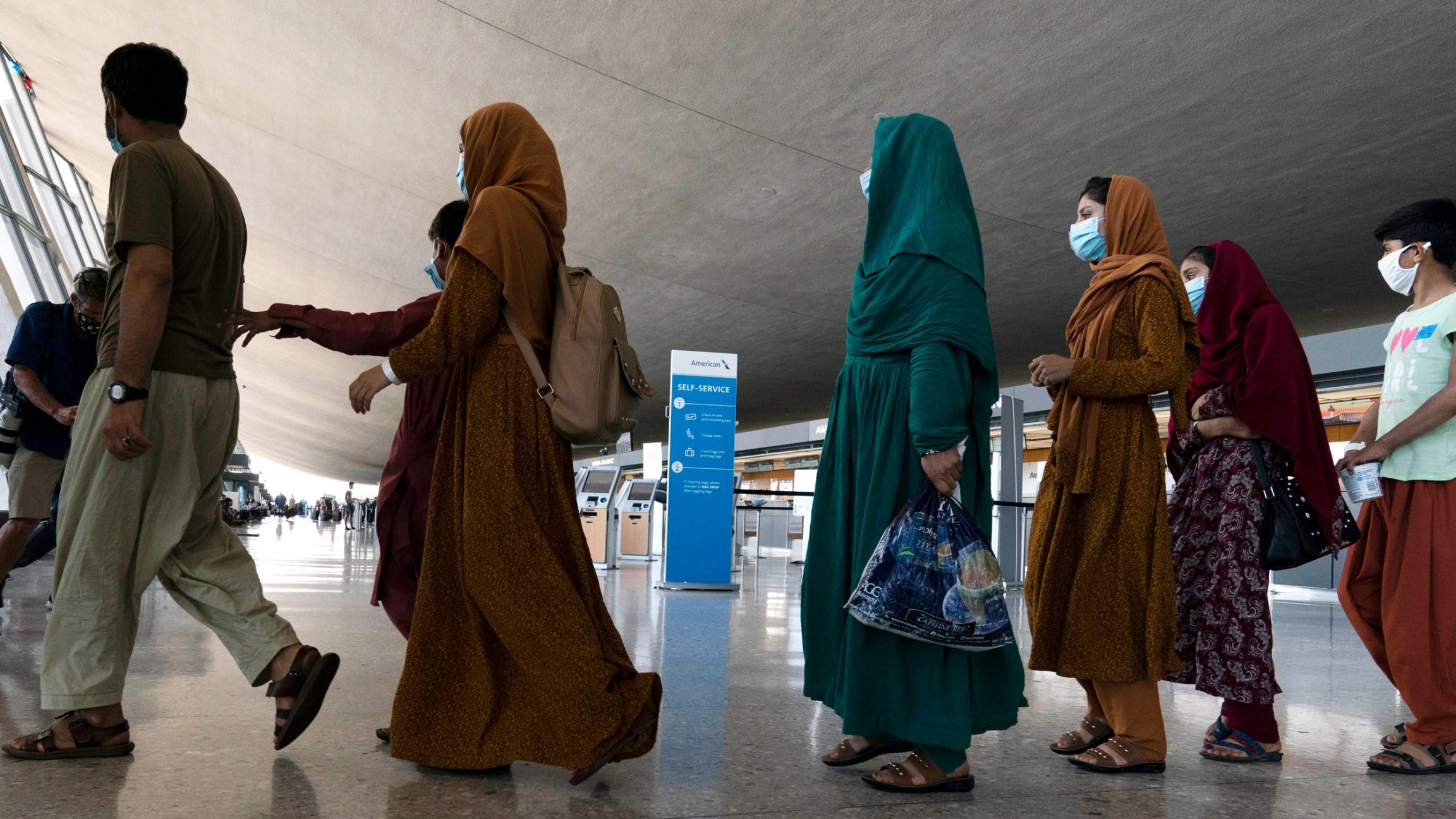 Families evacuated from Kabul, Afghanistan, walk through the terminal before boarding a bus after they arrived at Washington Dulles International Airport, in Chantilly, Virginia, on Friday, Aug. 27, 2021.
