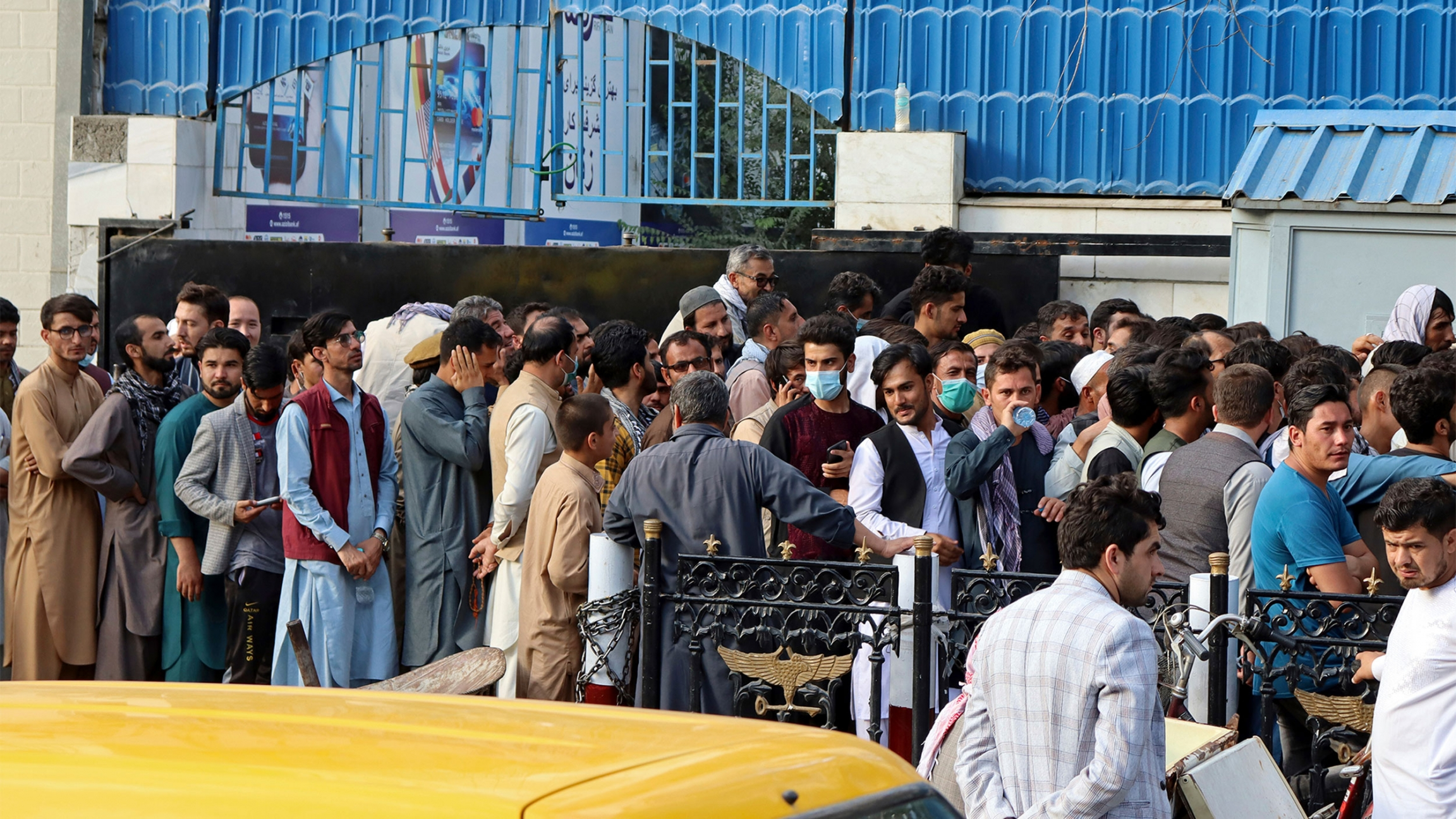 Afghans wait in long lines for hours to try to withdraw money, in front of a Bank in Kabul, Afghanistan