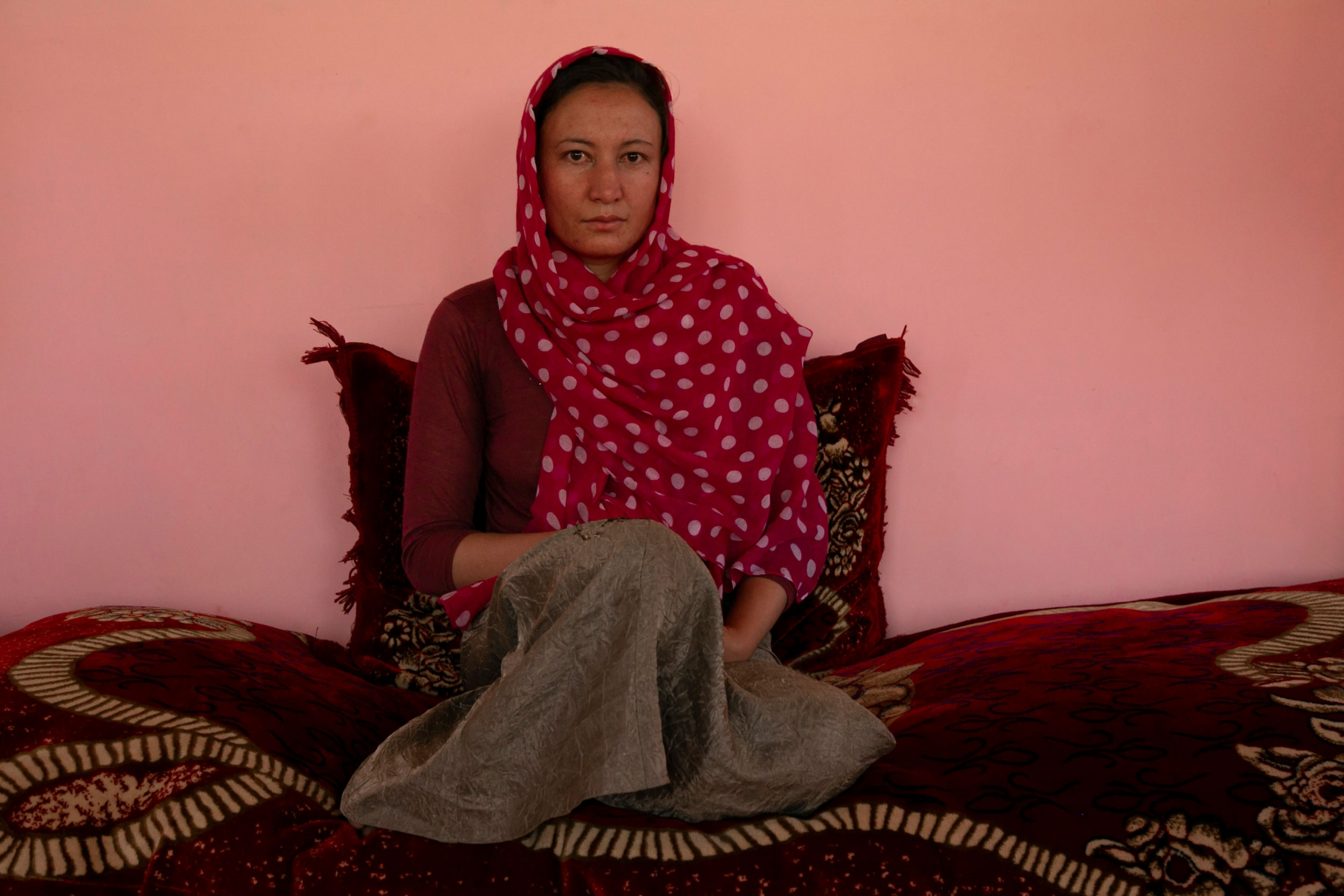 A woman is shown sitting on a large cushion and wearing a red and white polka dot scarf.
