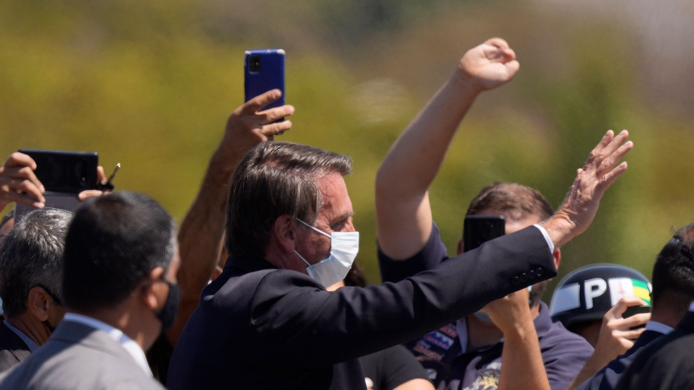 Brazilian President Jair Bolsonaro waves to people during a ceremony marking Soldier Day at Army headquarters in Brasilia, Brazil, Aug. 25, 2021.