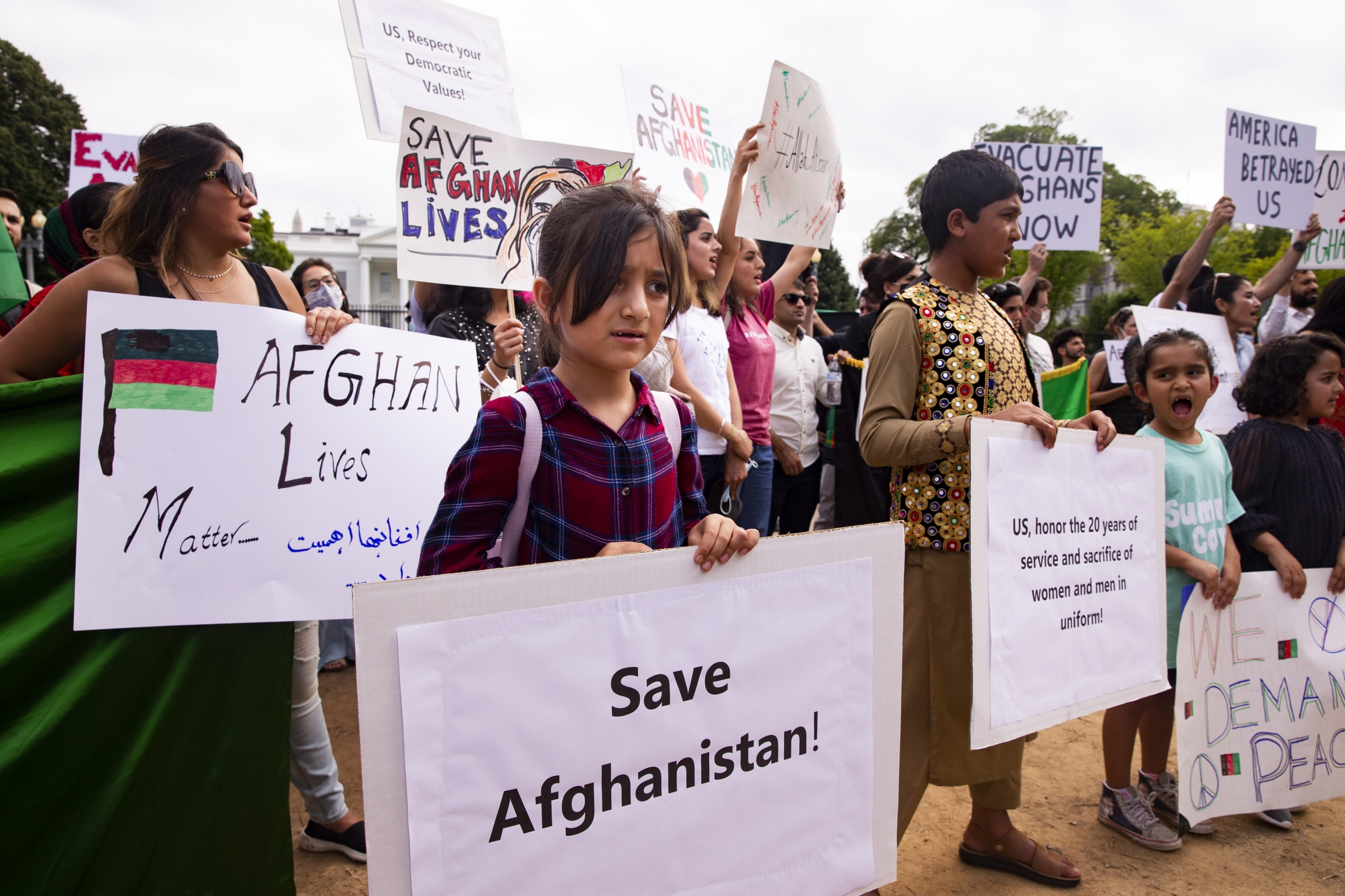 """Women holding signs saying """"save Afghan lives"""" and """"Afghan Lives Matter"""" at a protest, with the White House in the background"""