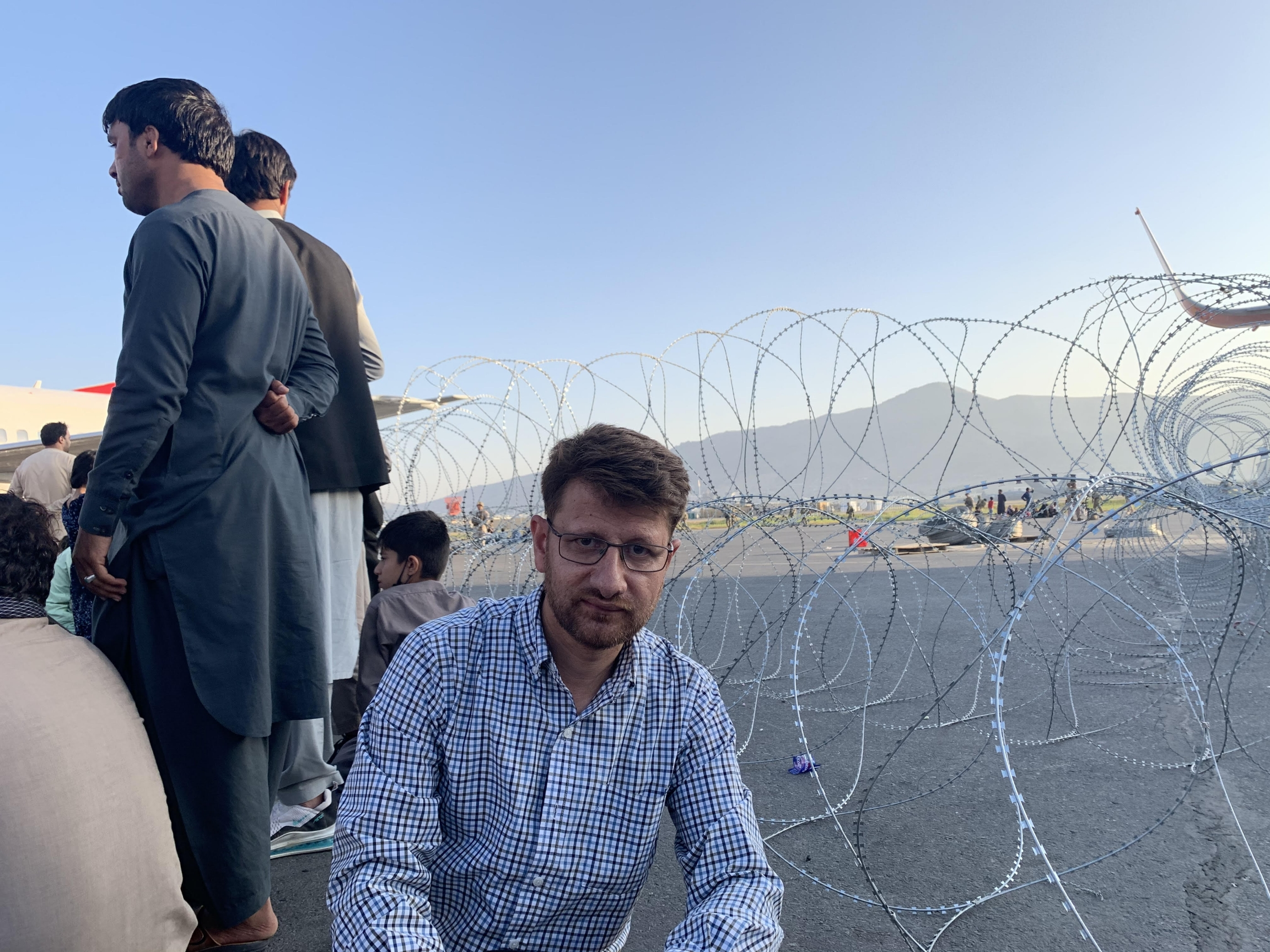 Hanif Sufizada kneeling besides a coil of barbed wire on the airport tarmac, amid a crowd of civilians