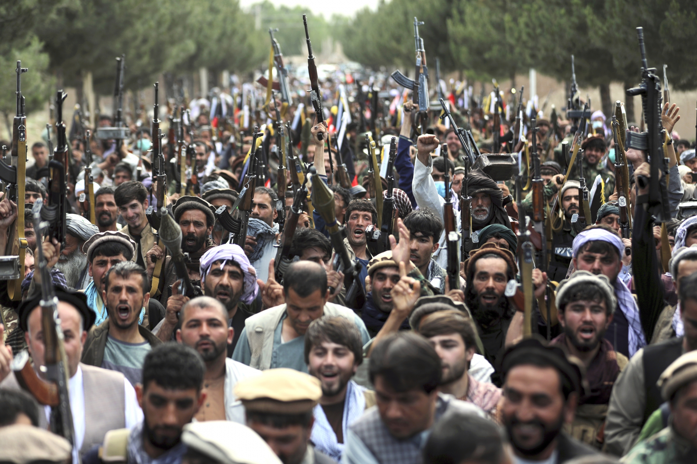 A crowd of Taliban fighters in a road, holding automatic rifles in the air