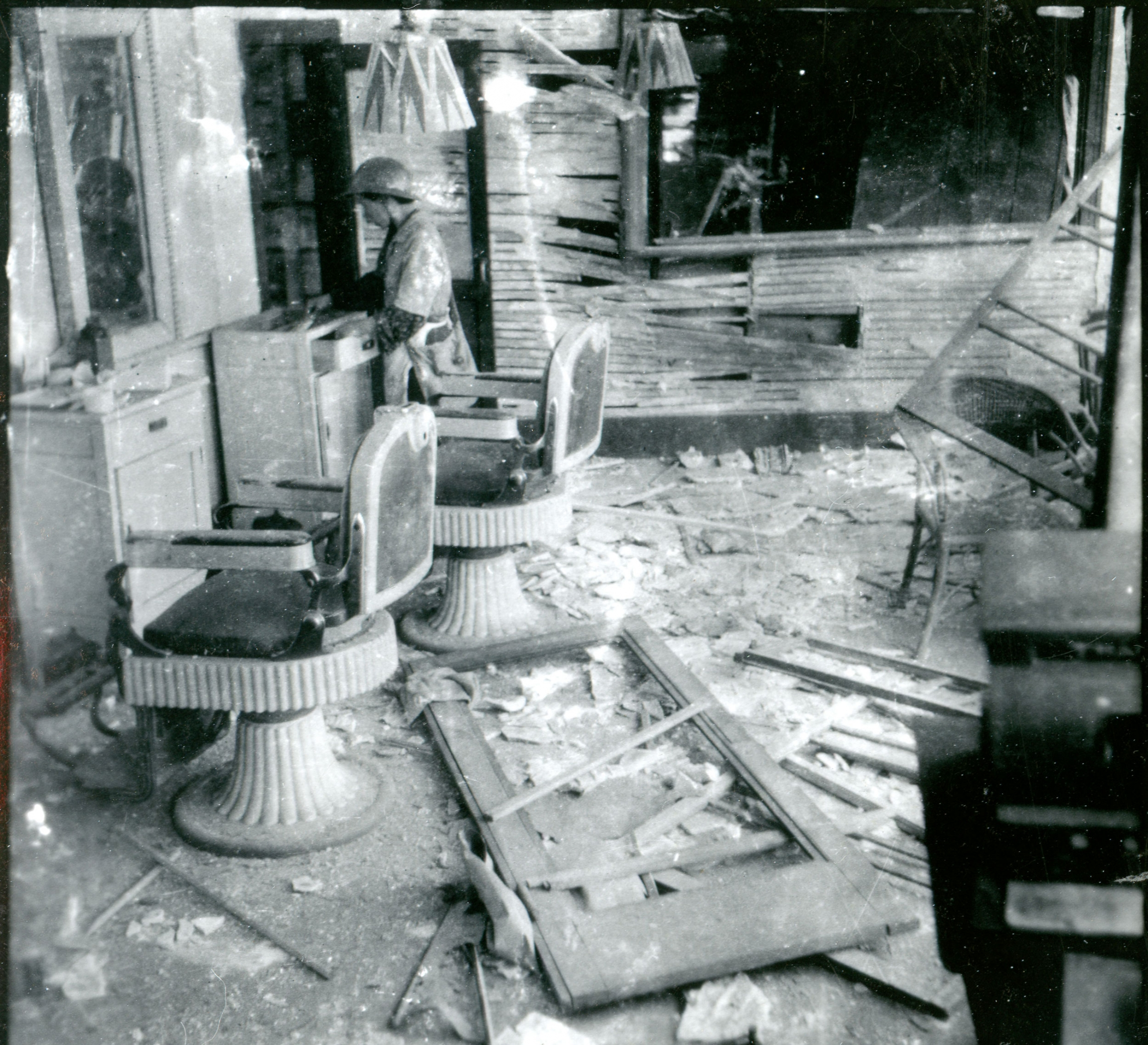 Two barbershop chairs are shown with broken glass on the floor and a woman looking through a drawer.