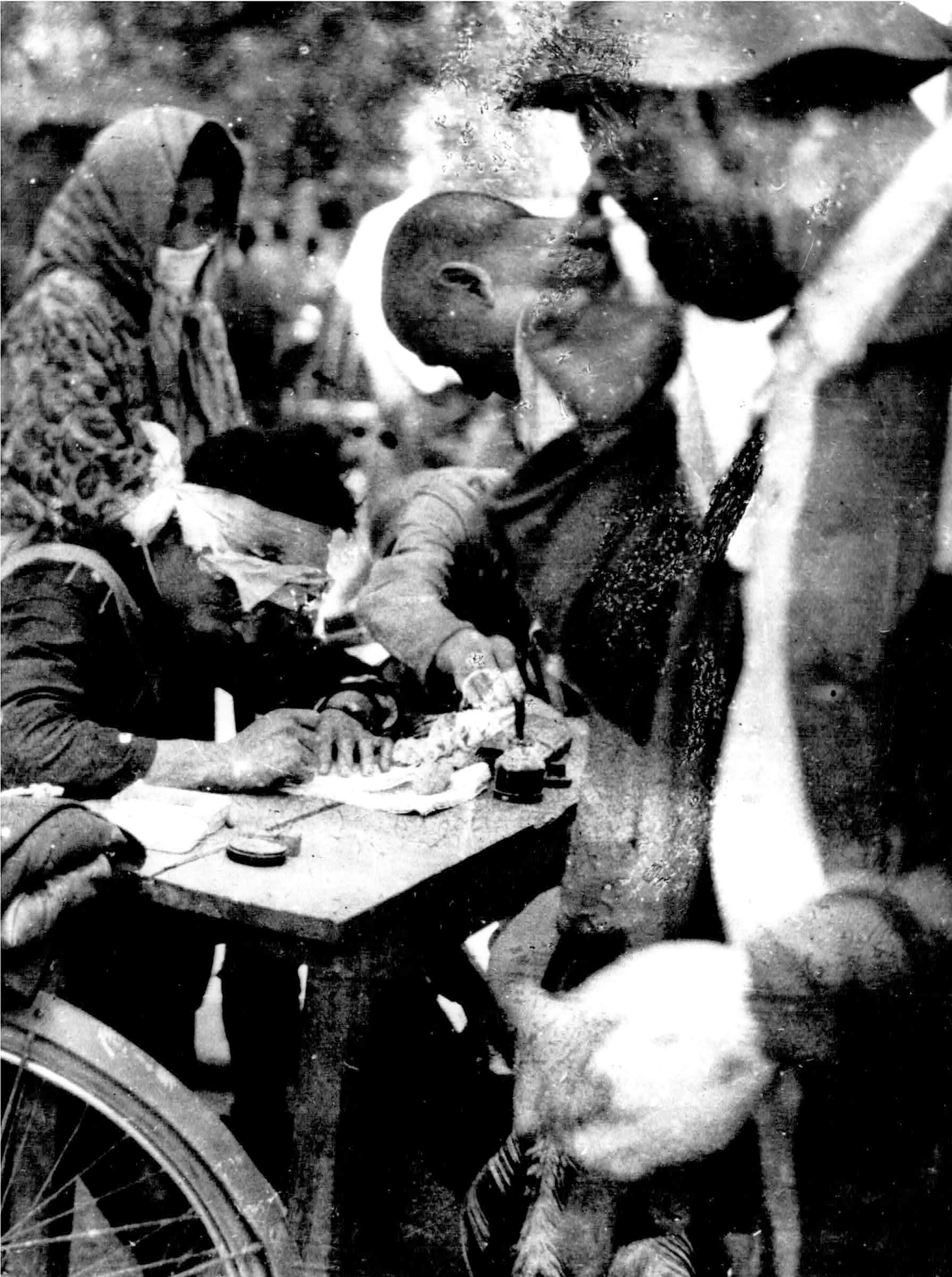 A police officer is shown sitting at a table while wearing a bandage on his head and writing on paper with several people standing around him.