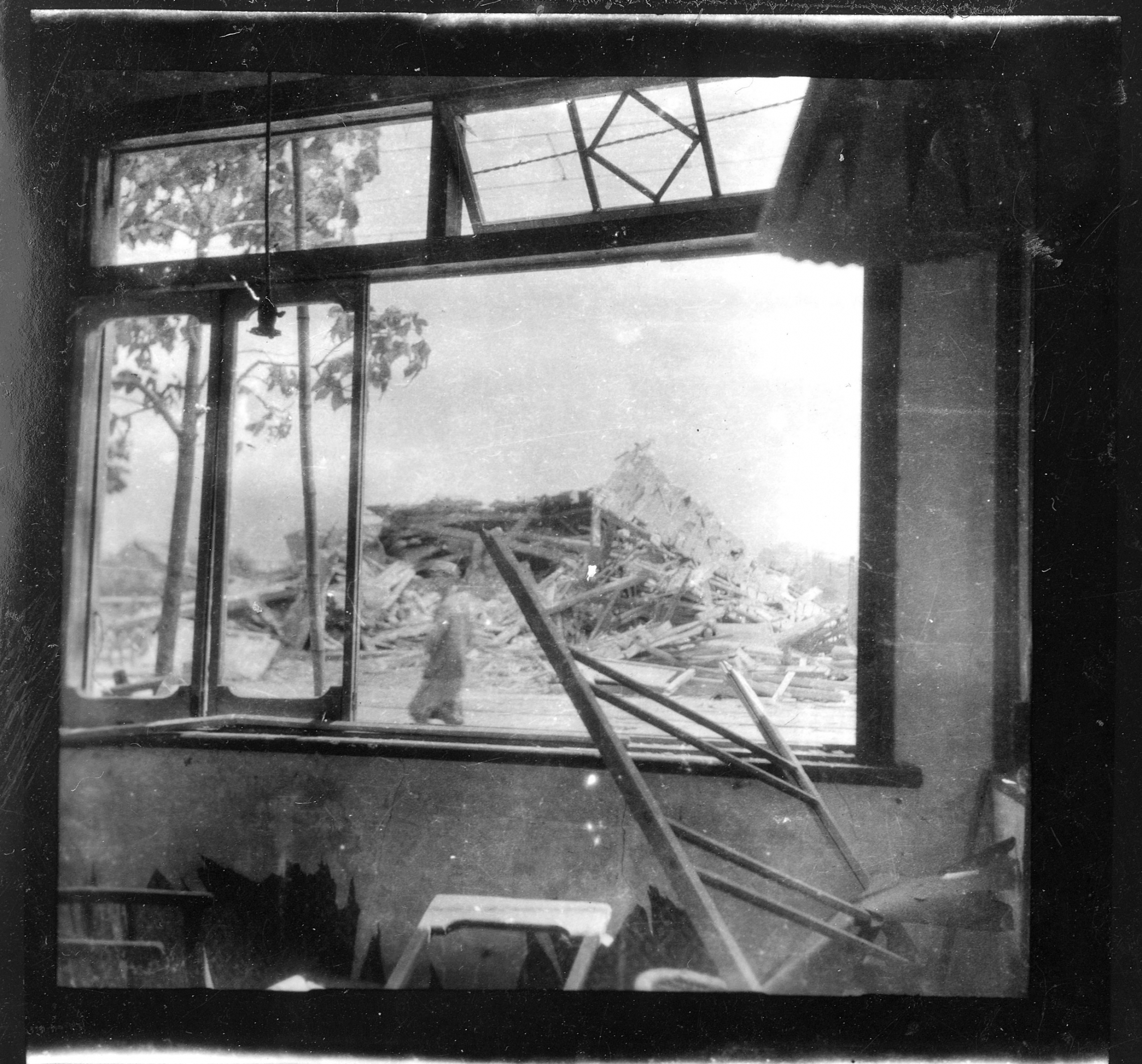 A pile of wooden rubble in the distance is shown through a blasted out window.