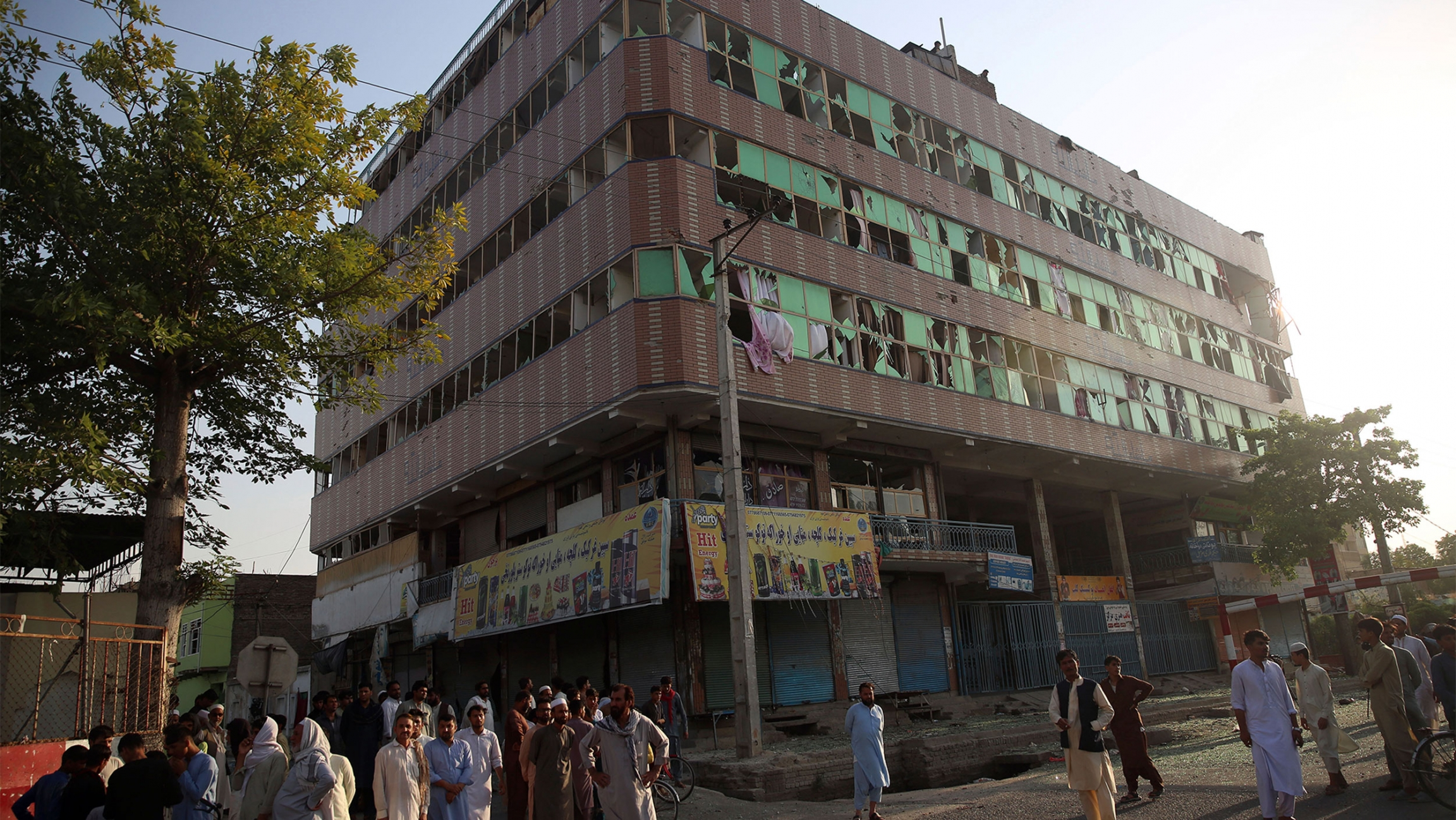 Afghan people are seen near the building where insurgents were hiding during an attack to the prison in the city of Jalalabad, east of Kabul, Afghanistan.