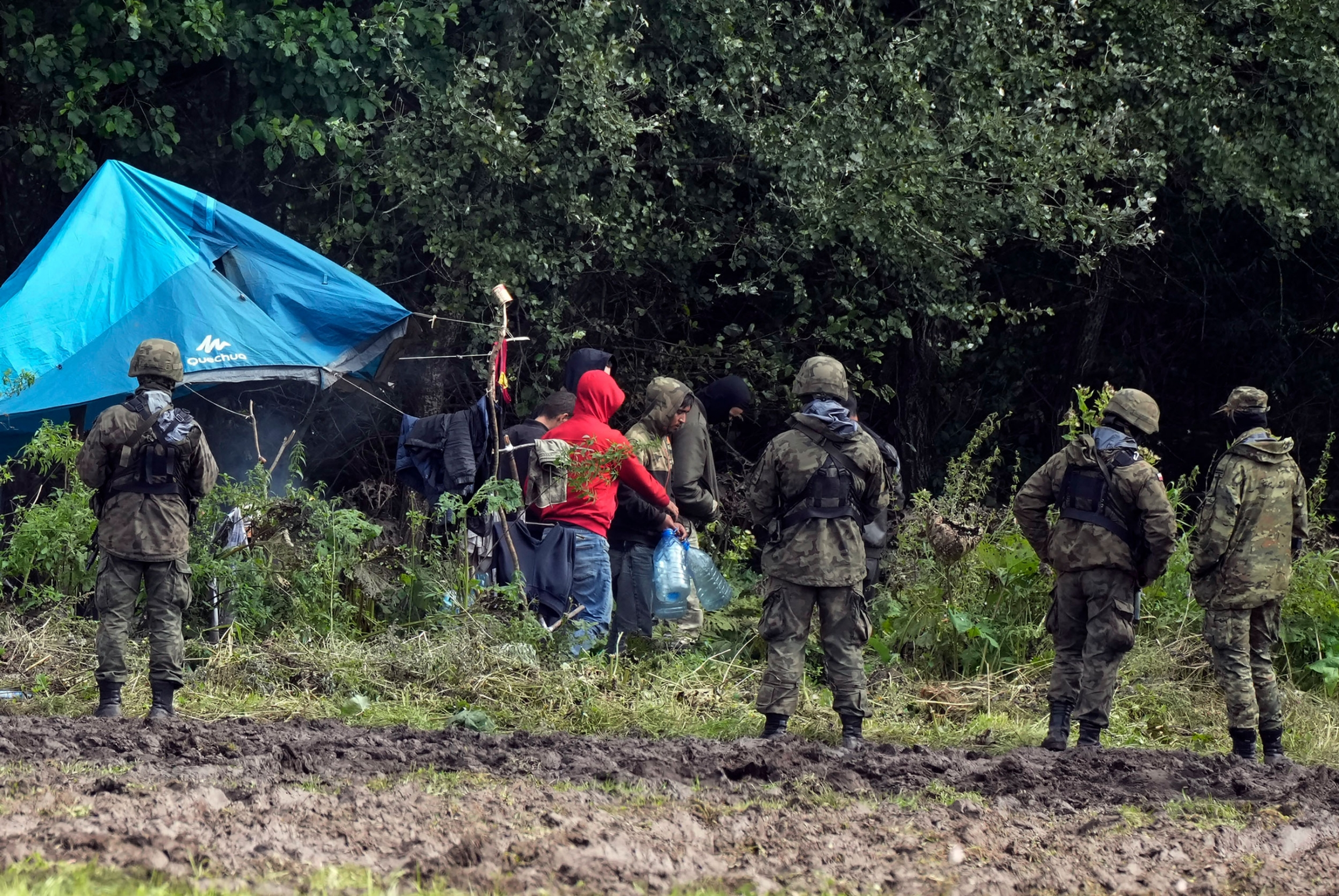 Migrants stuck along the Poland-Belarus border carry plastic water bottles as they are surrounded by Polish forces in Usnarz Gorny, Poland, on Wednesday, Sept. 1, 2021.