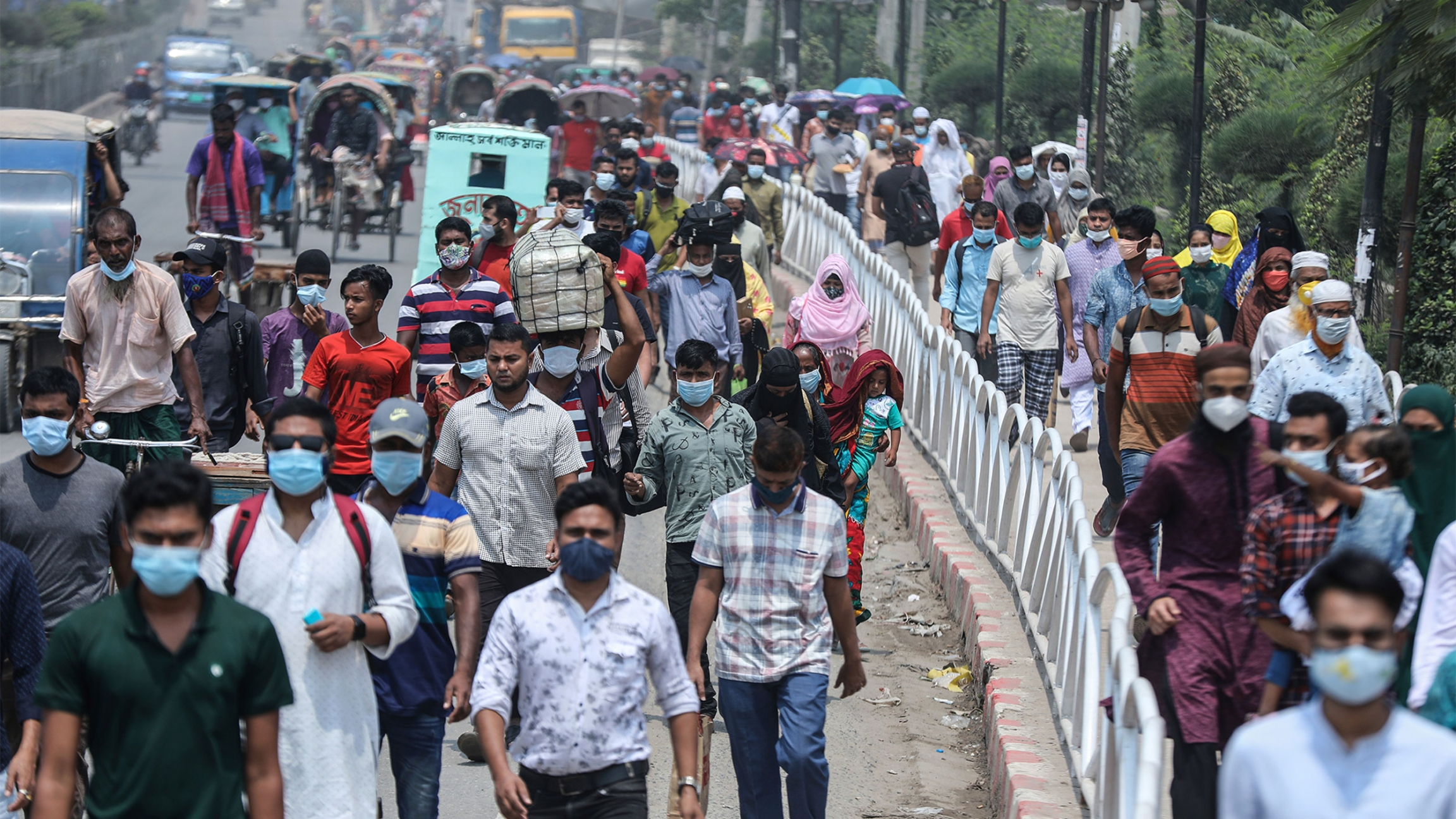 People wearing face masks as a precaution against the coronavirus leave the city to travel to their native places ahead of Eid al-Fitr in Dhaka, Bangladesh