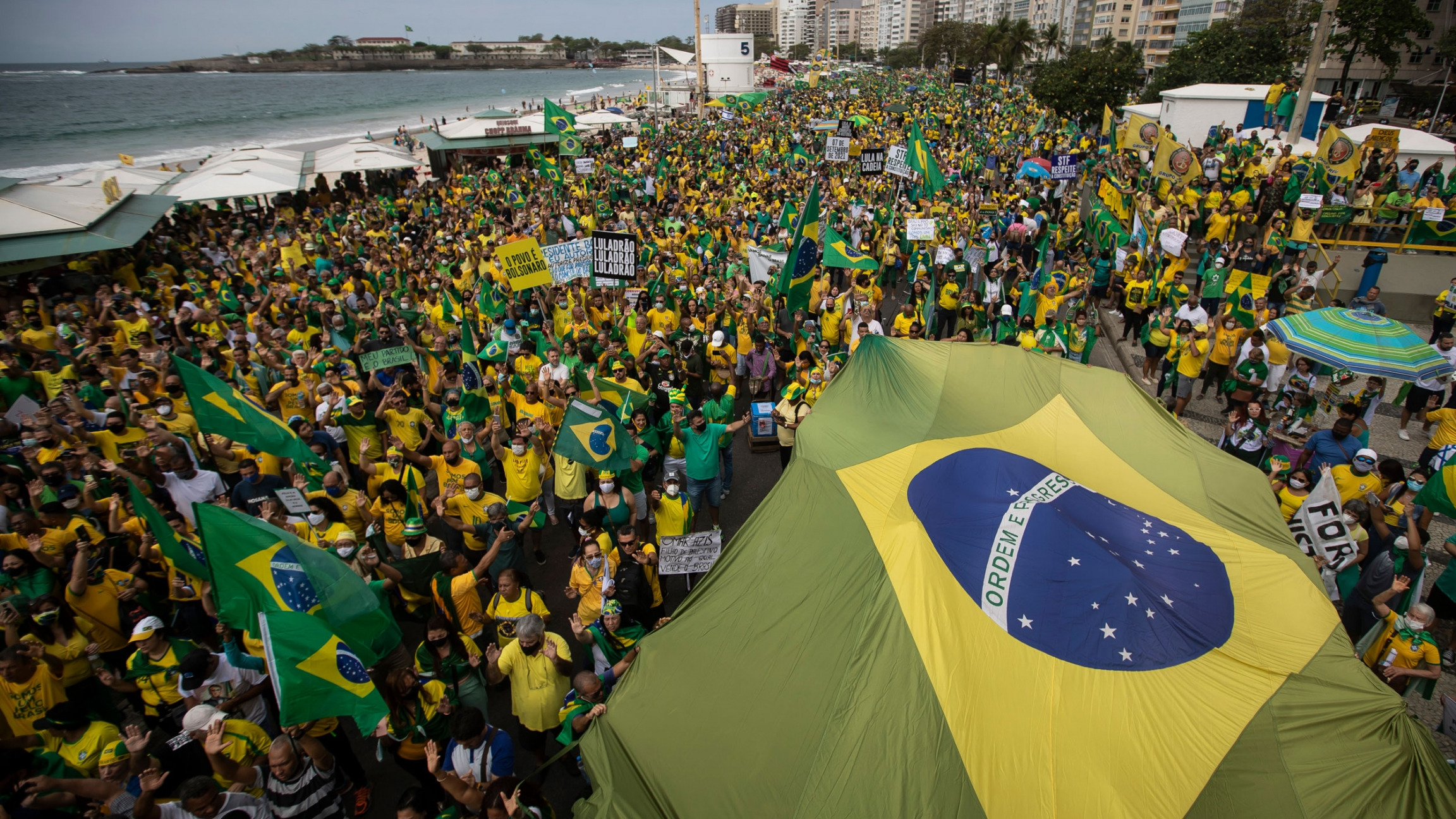 Supporters of Brazilian President Jair Bolsonaro carry Brazil's national flag along Copacabana Beach on Independence Day in Rio de Janeiro, Brazil, Tuesday, Sept. 7, 2021.