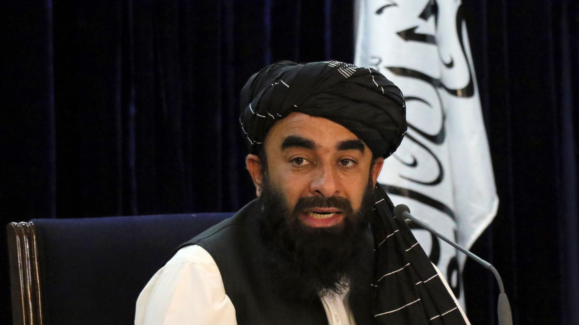 Taliban spokesman Zabihullah Mujahid is shown sitting while wearing a dark head wrap and black vest with the Taliban flag behind him.
