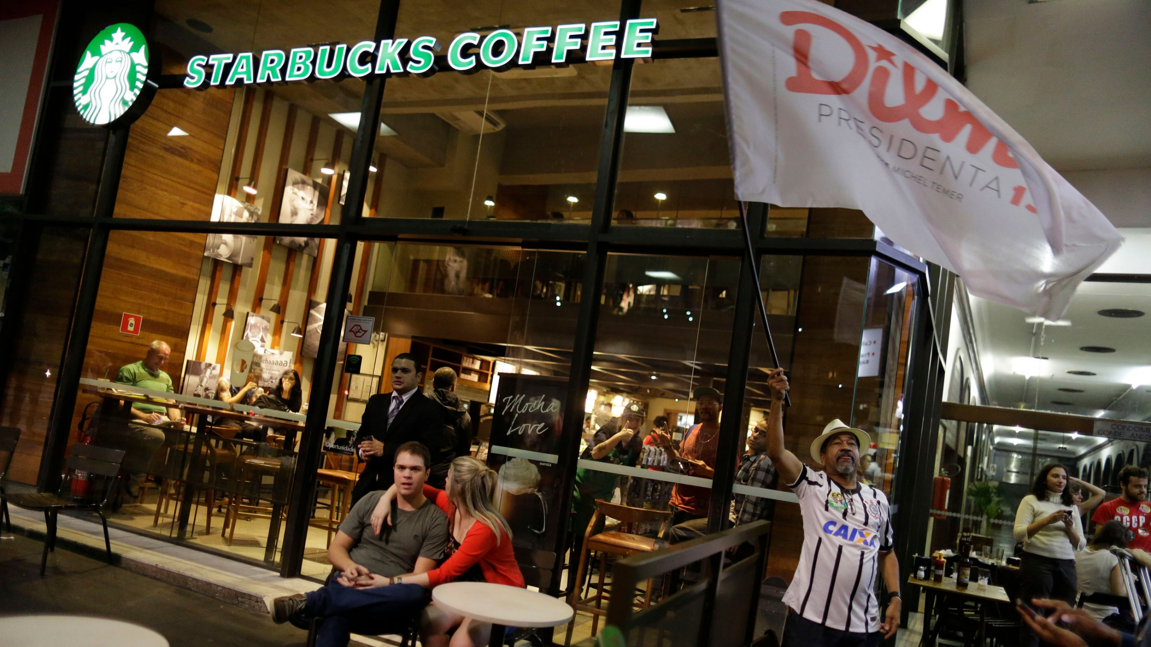 Brazilians gather in front of a Starbucks coffee shop in Sao Paulo, Brazil, Sunday, Oct. 26, 2014. Recent extreme weather events have taken a toll on Brazil's coffee crops, straining the global coffee supply chain.