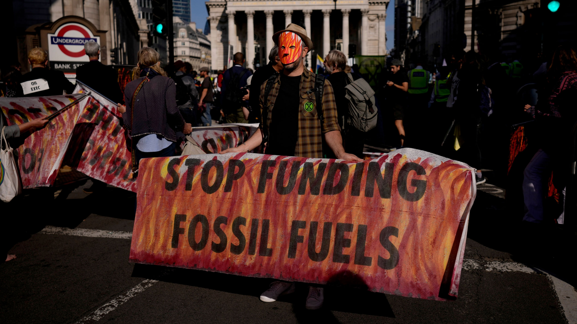 In this Thursday, Sept. 2, 2021 file photo, an Extinction Rebellion climate change activist holds a banner backdropped by the Bank of England, at left, and the Royal Exchange, center, in the City of London financial district in London.