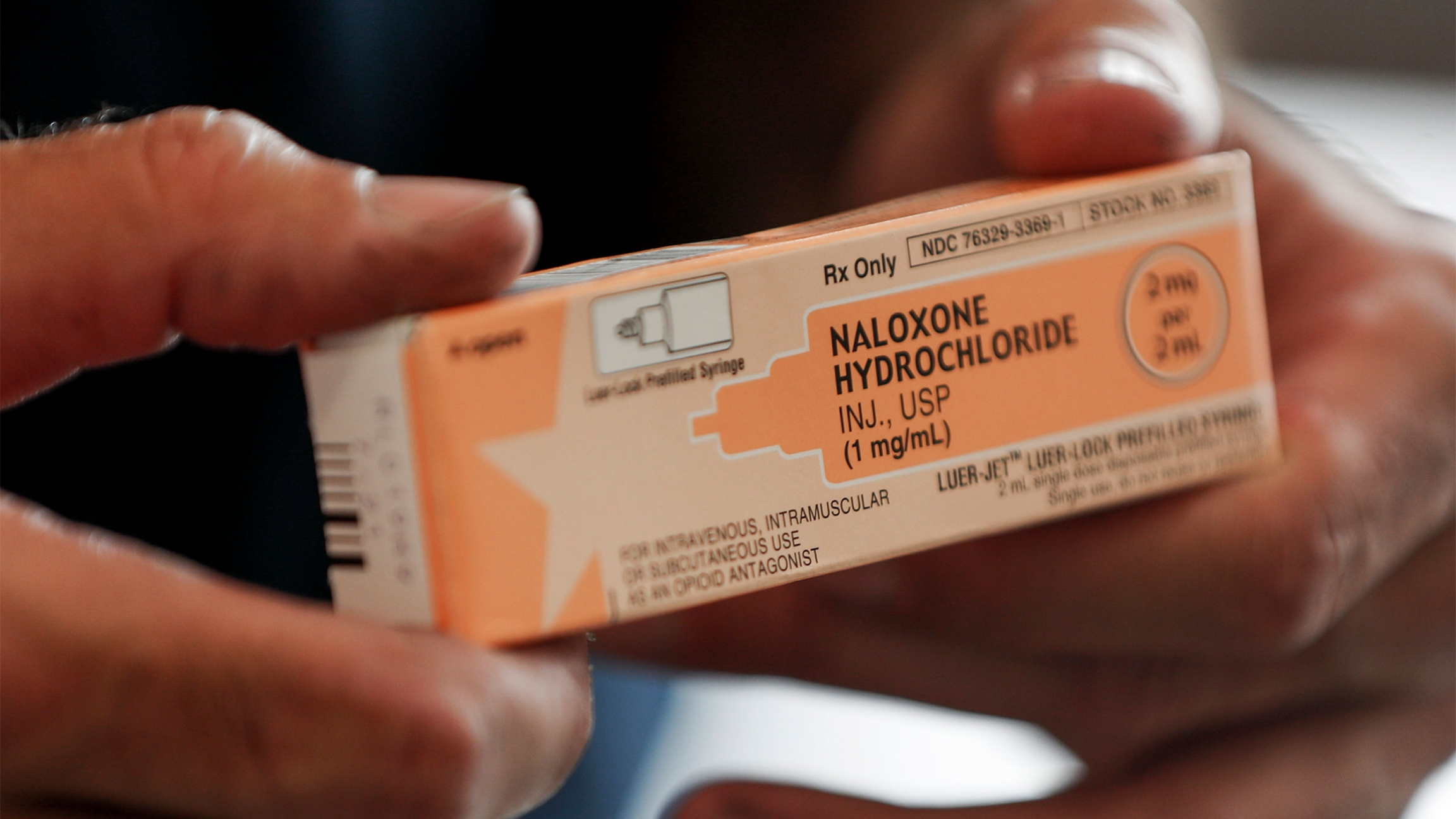 A fire medic holds a box containing naloxone hydrochloride which is carried in all their department's emergency response vehicles, in Akron, Ohio